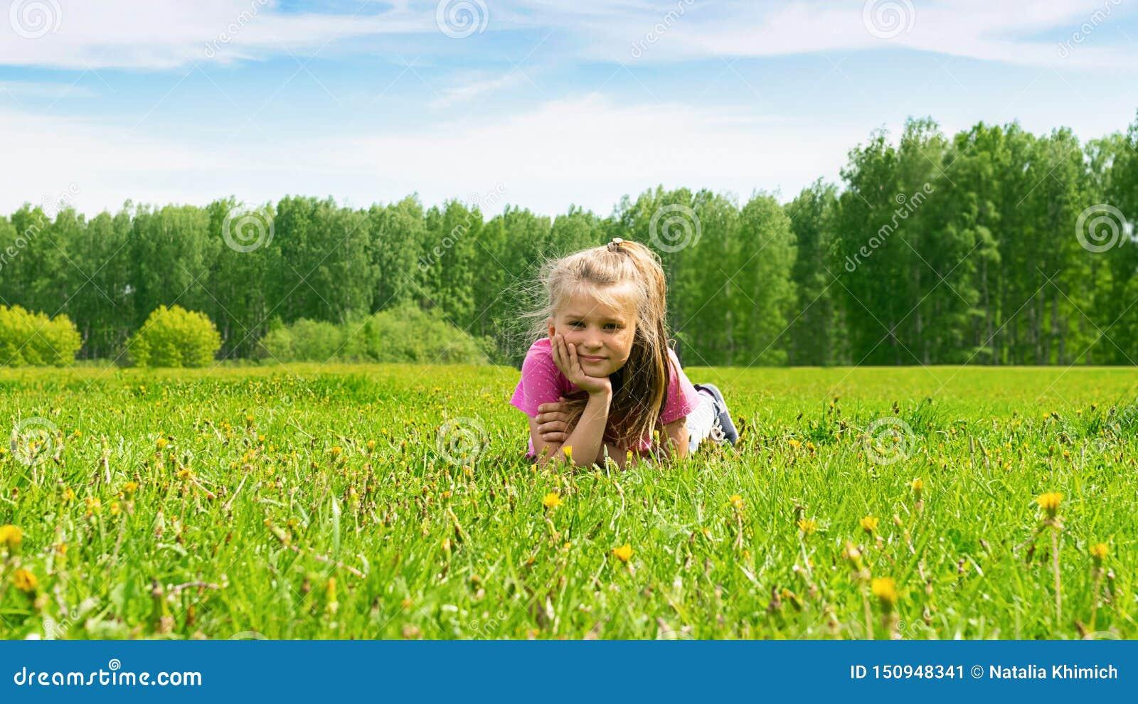 Portret van een klein meisje dat op een groene weide in vers gras ligt Het concept van de zomer Selectieve nadruk De ruimte van h