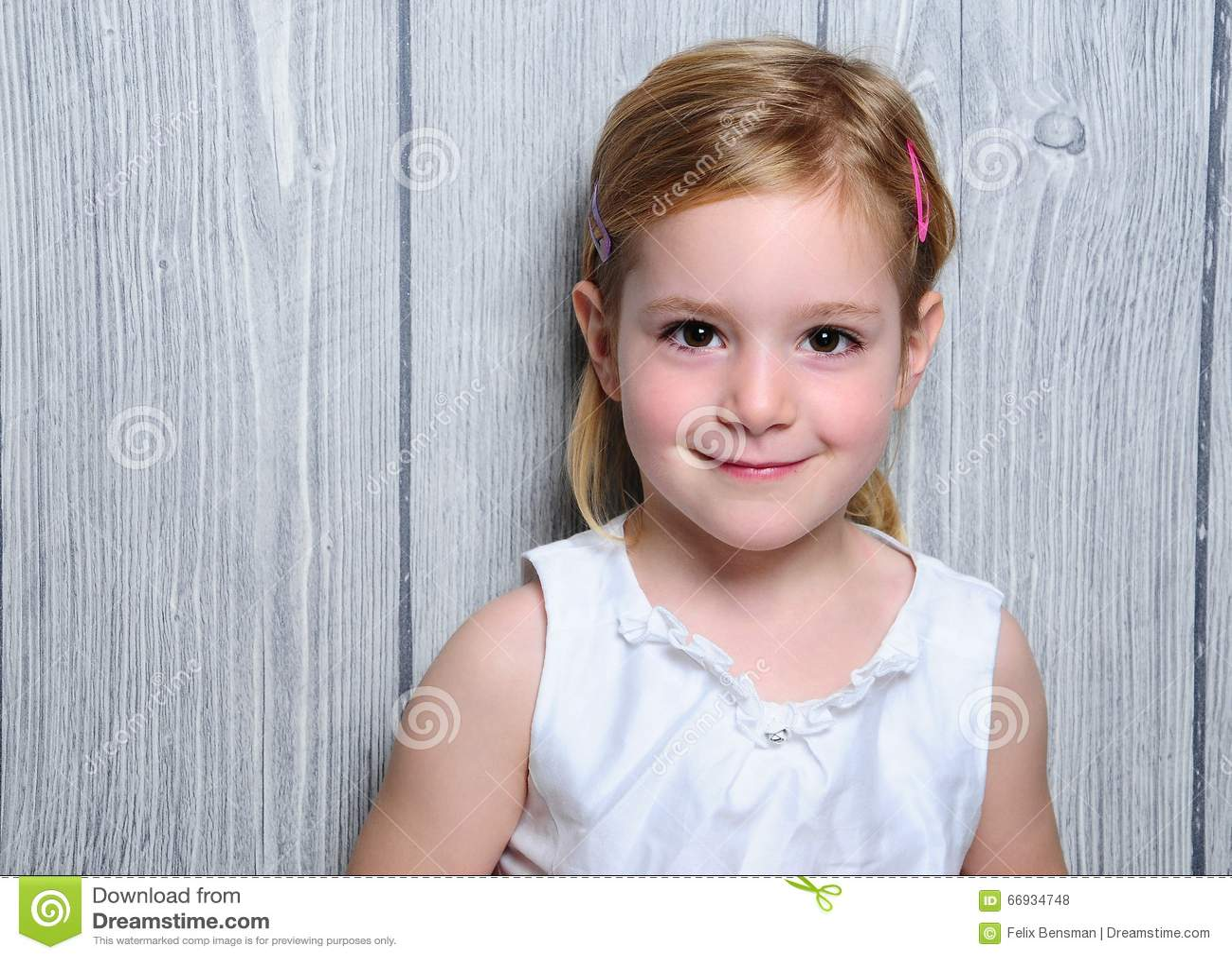 Portret van een leuk glimlachend blondemeisje van vier jaar in witte kleding en kleurrijke haarspeldjes in haar haar
