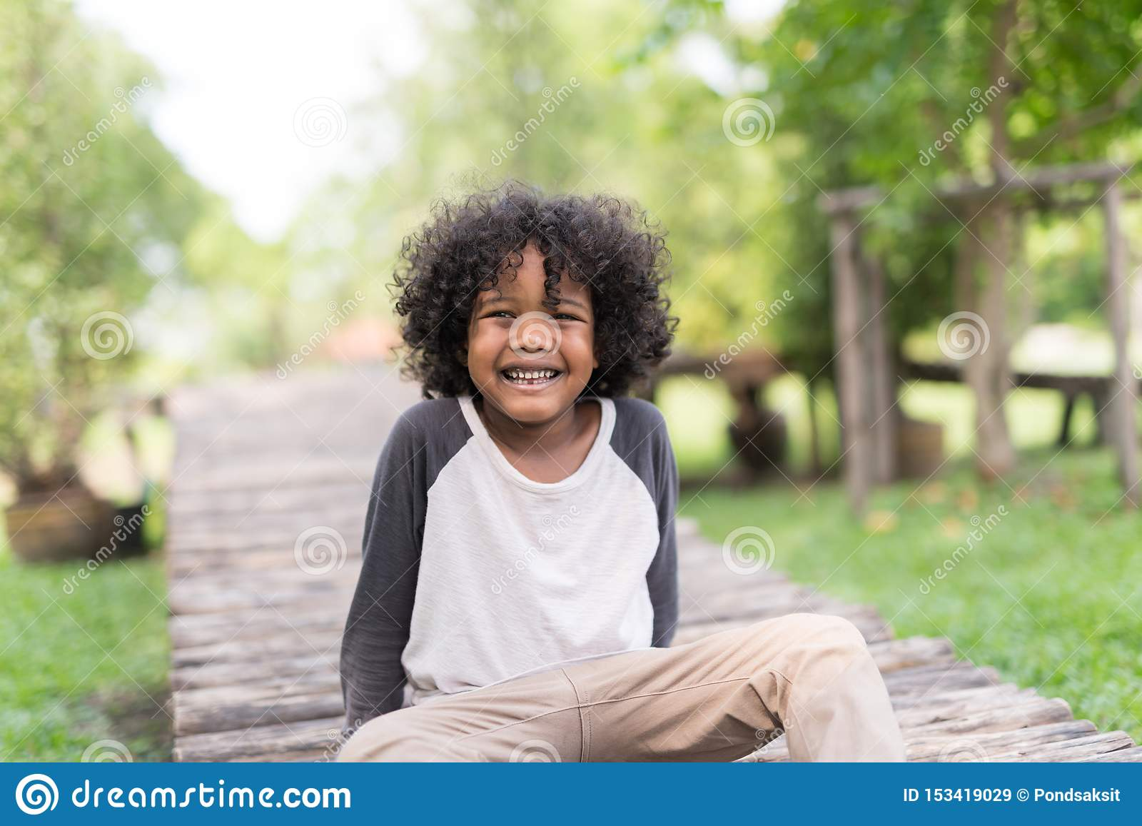 Portret van een leuke Afrikaanse Amerikaan weinig jongen die bij aardpark glimlachen