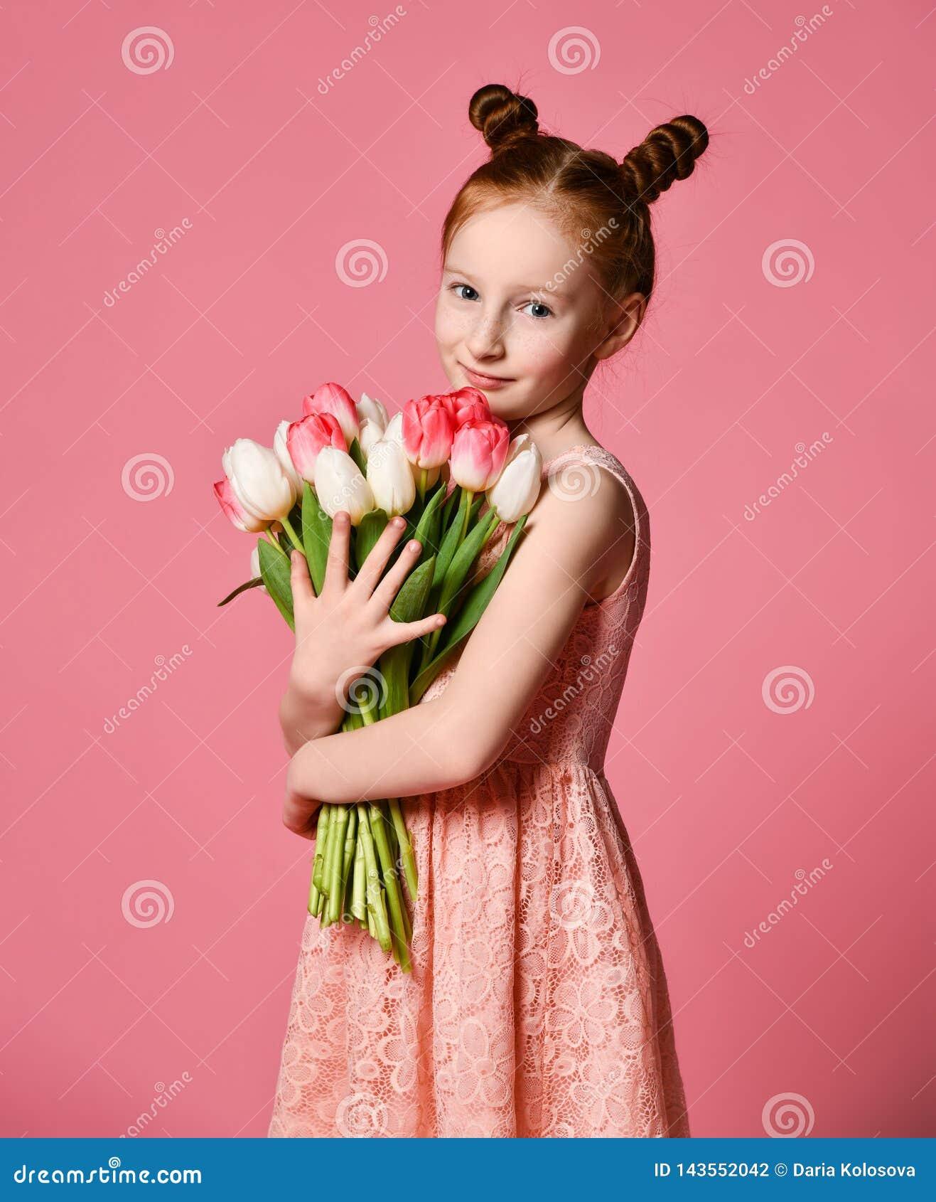 Portret van een mooi jong meisje die in kleding groot die boeket van irissen en tulpen houden over roze achtergrond worden geïsol