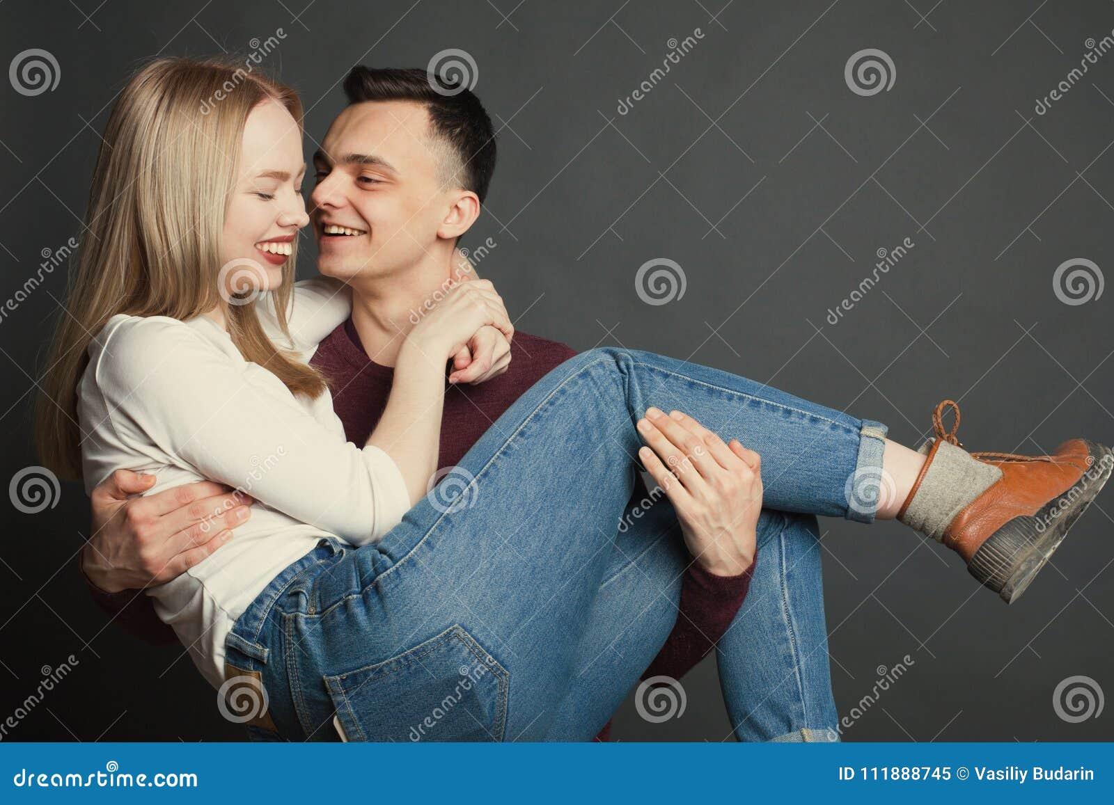 Portret van een mooi jong paar in liefde het stellen bij studio over donkere achtergrond De kerel houdt zijn geliefd in zijn wape