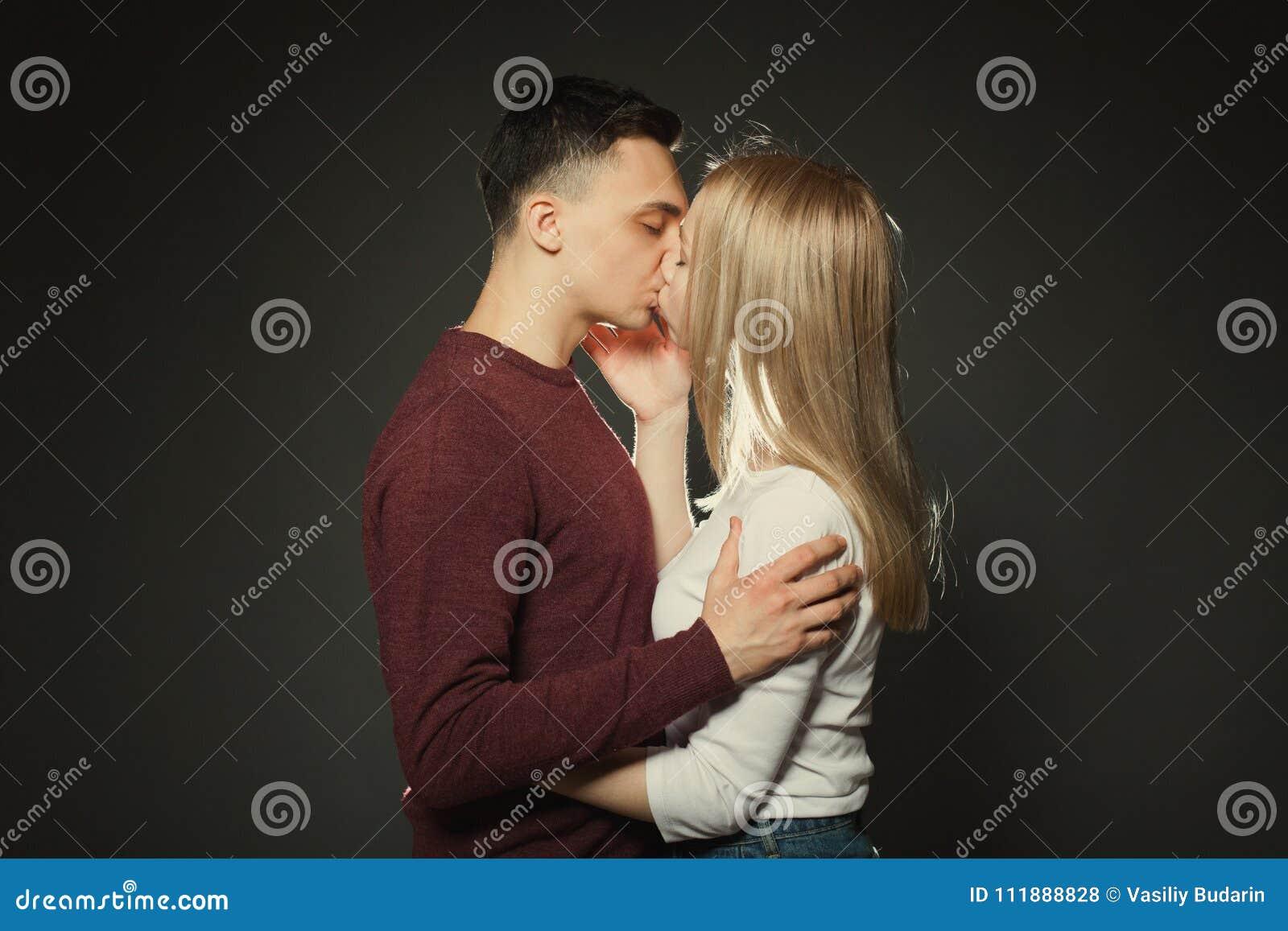 Portret van een mooi jong paar in liefde het stellen bij studio over donkere achtergrond Kerel en meisje die dicht omhoog kussen