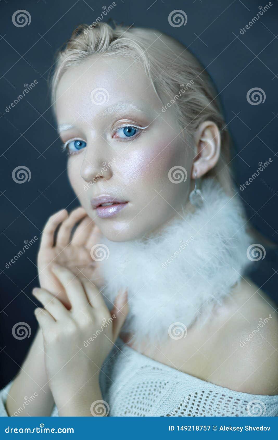 Portret van een mooi meisje in de vorst op zijn gezicht op een blauwe ijsachtergrond