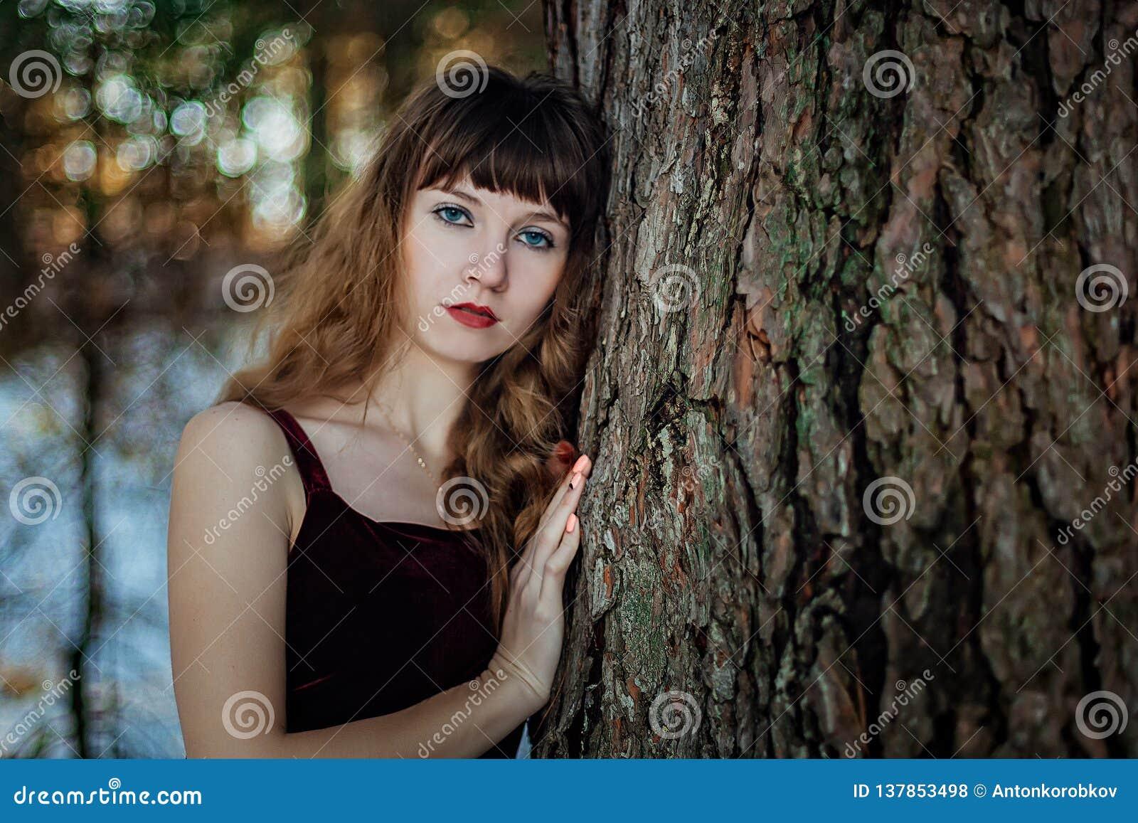 Portret van een mooi meisje in een donkere lange kleding die zich alleen onder de bomen in het de winterbos bevindt