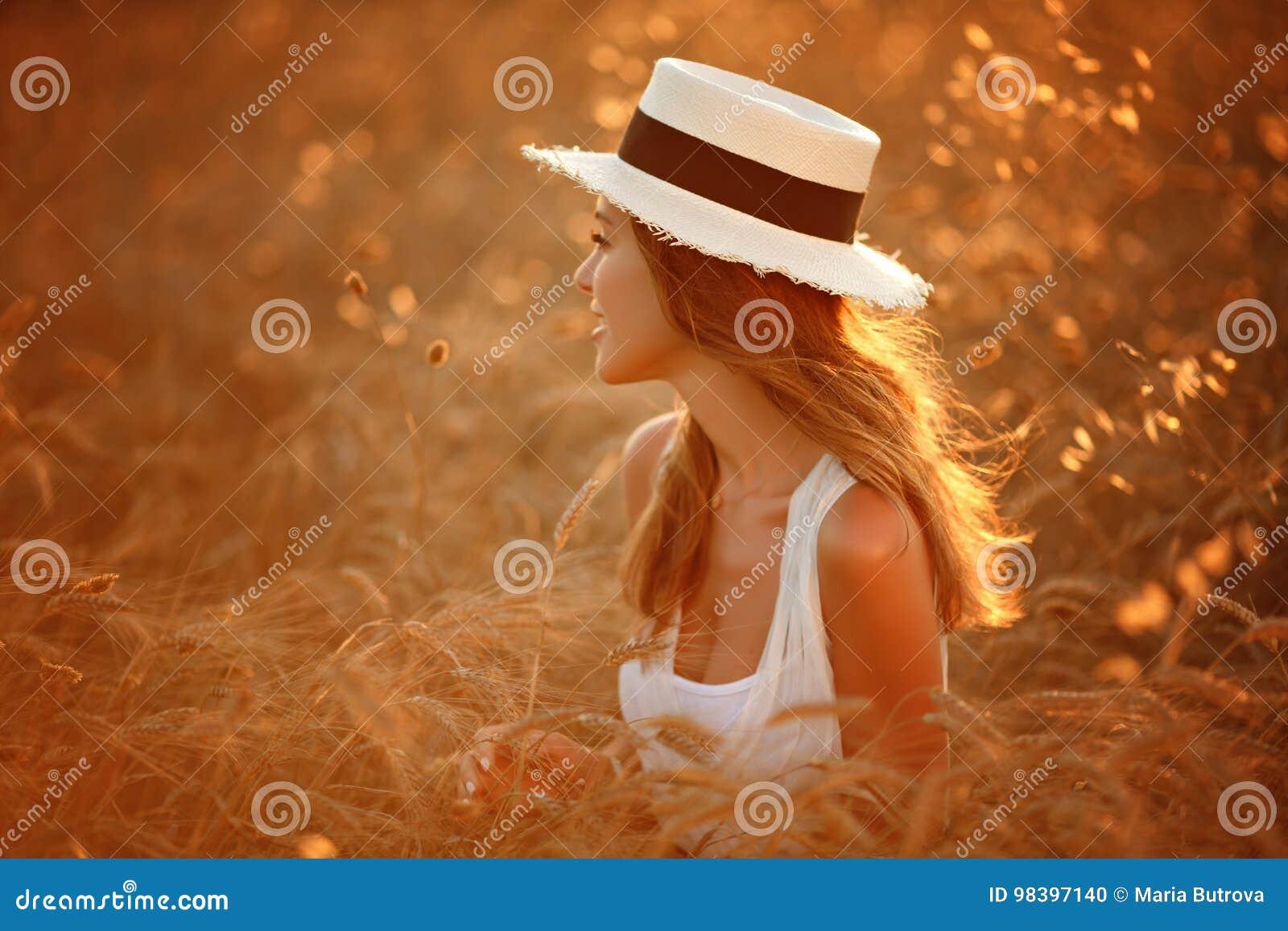 Portret van een mooi meisje in een witte kleding en hoed in fie