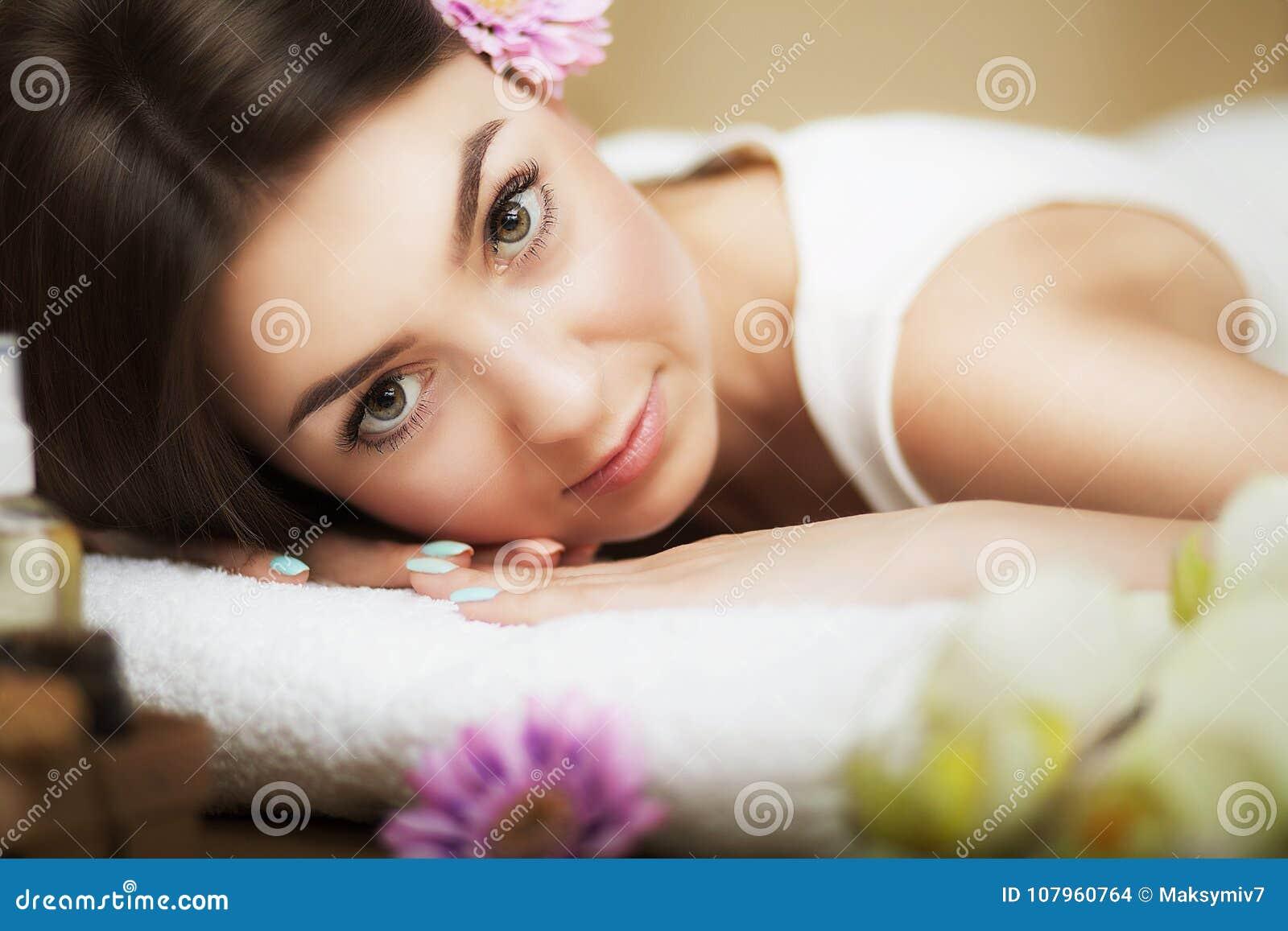 Portret van een mooi meisje in een kuuroord Verzacht blik Bloemen in haar Aromaolie Massagekabinet Het concept gezondheid en scho
