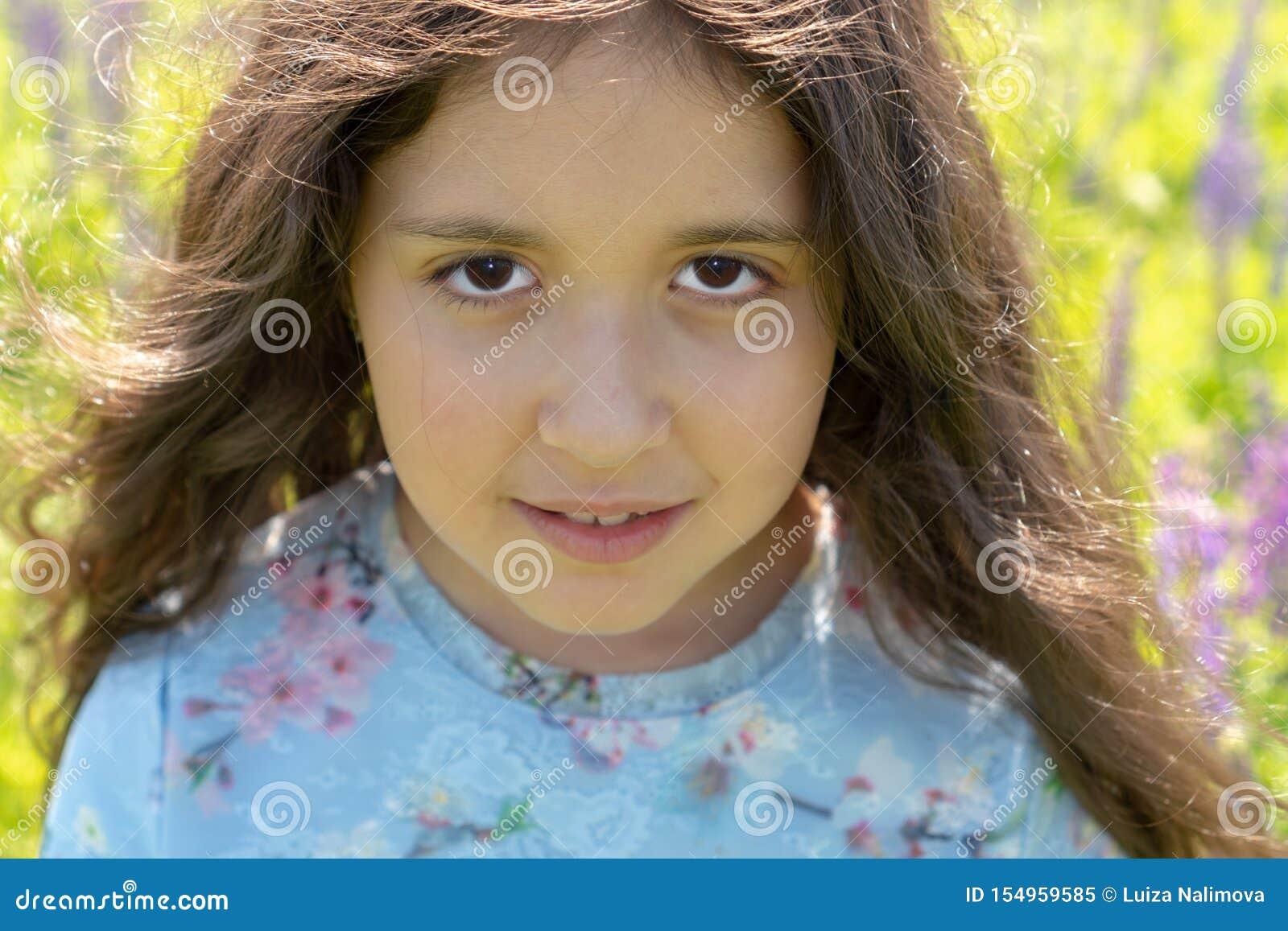 Portret van een mooi Moslimtienermeisje met bruine ogen en lang, krullend haar op een gebied van bloemen