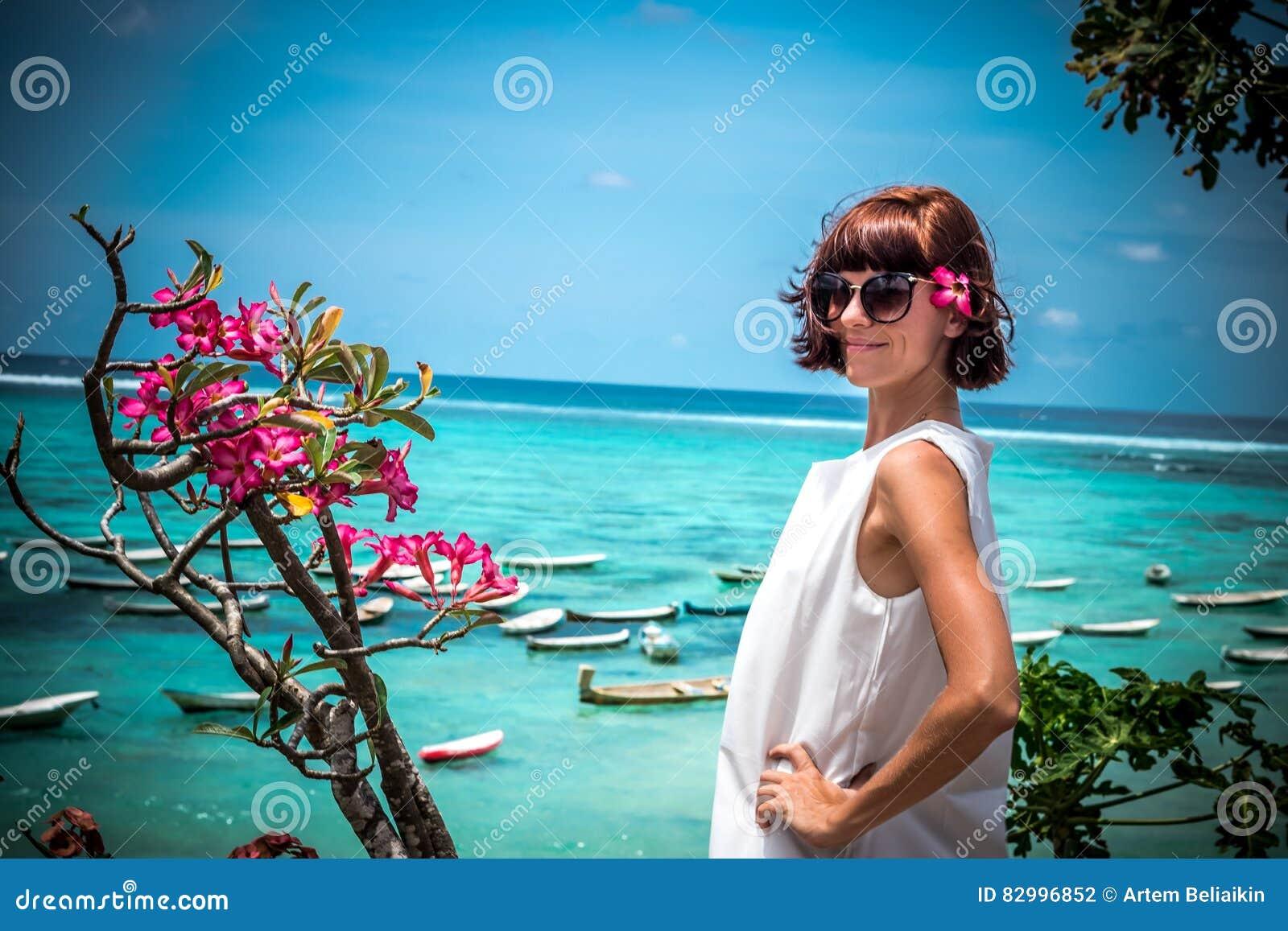 Portret van een mooie gezonde jonge vrouw dichtbij de oceaan met blauwe water en bloemen Tropisch eiland Bali, Indonesië