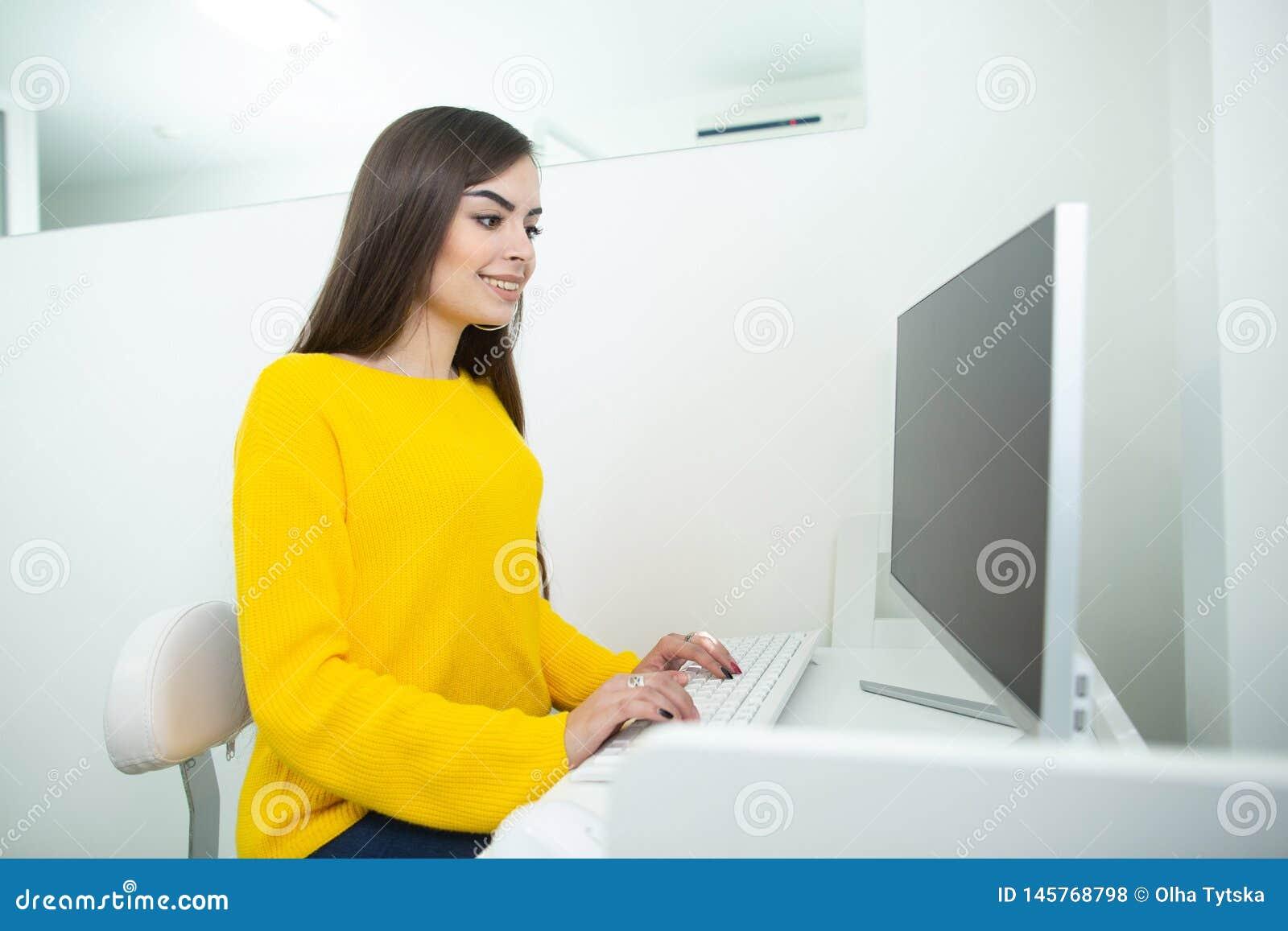 Portret van een mooie glimlachende vrouw die aan haar bureau in een bureaumilieu werken
