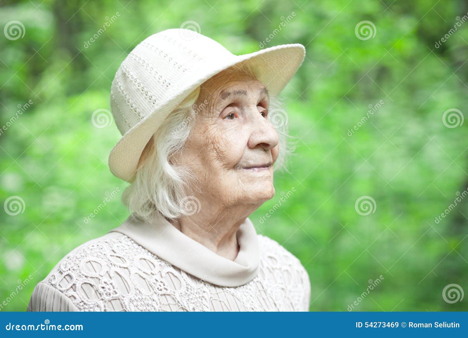 Portret van een mooie oude vrouw die in openlucht glimlachen
