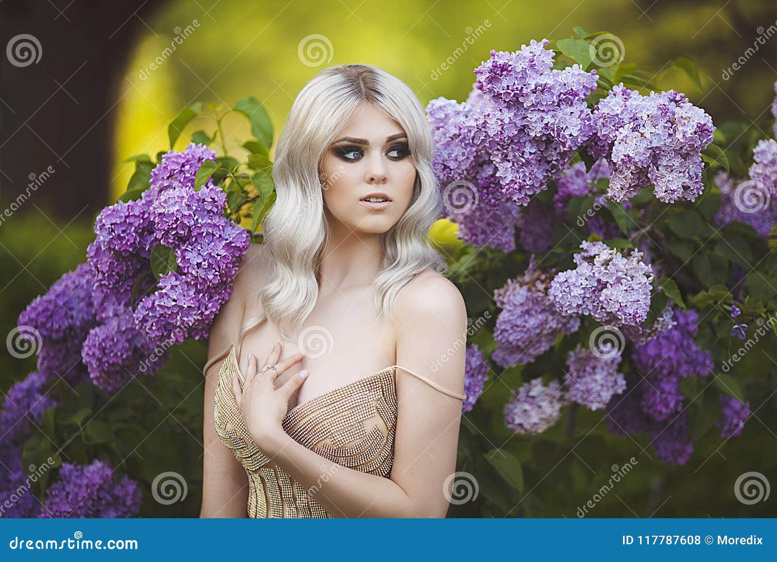 Portret van een mooie sensuele jonge blonde vrouw in de lente Tot bloei komende de lentetuin Jong meisje in een gouden kleding