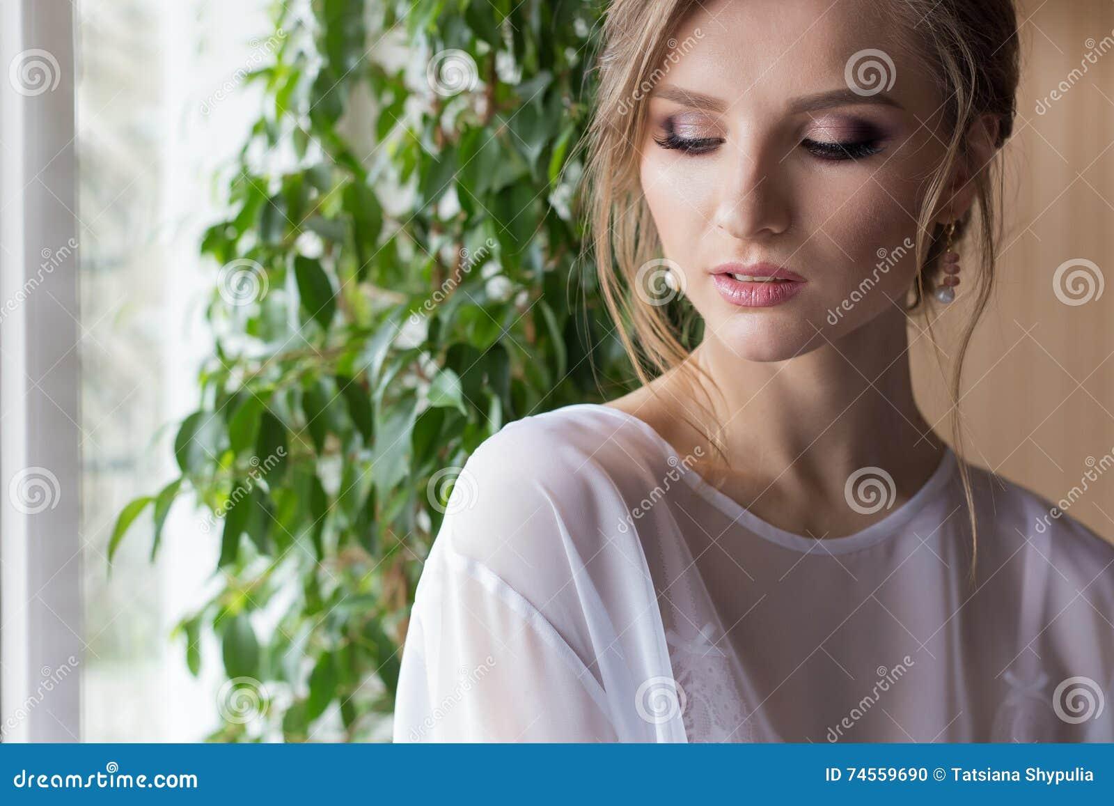 Portret van een mooie sexy leuke meisjesbruid in een witte kleding met gevoelig make-up en avondkapsel