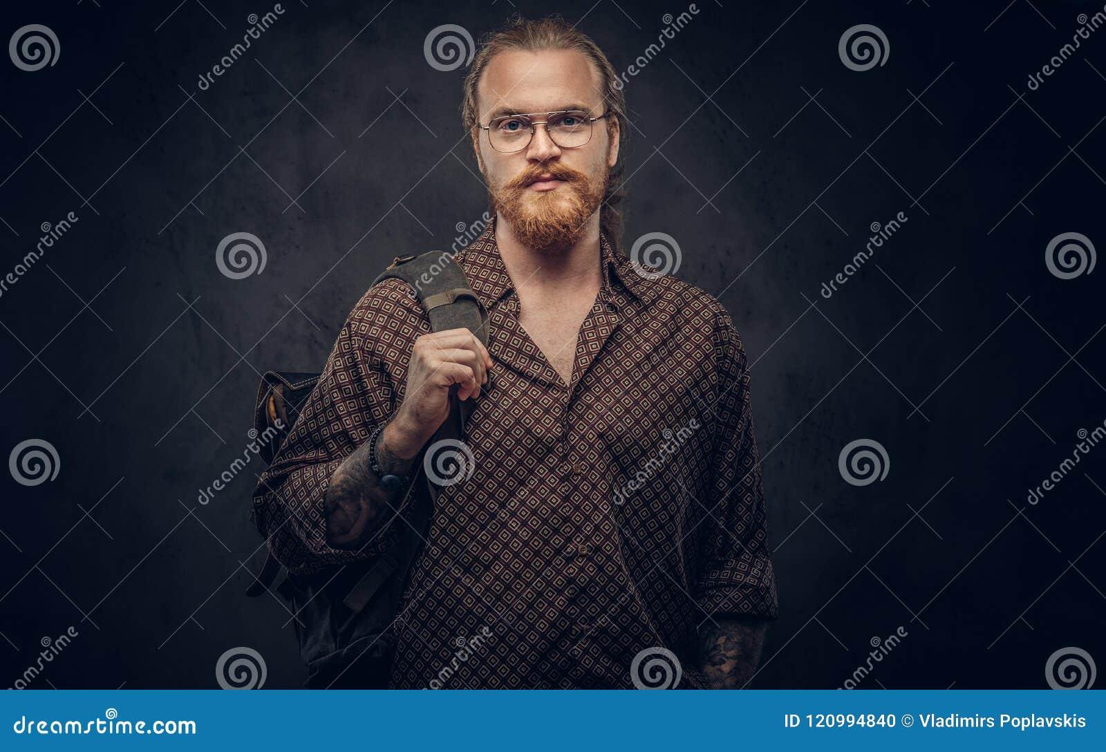 Portret van een roodharige hipster student in glazen gekleed in een bruin overhemd die, houdt een rugzak, bij een studio stellen