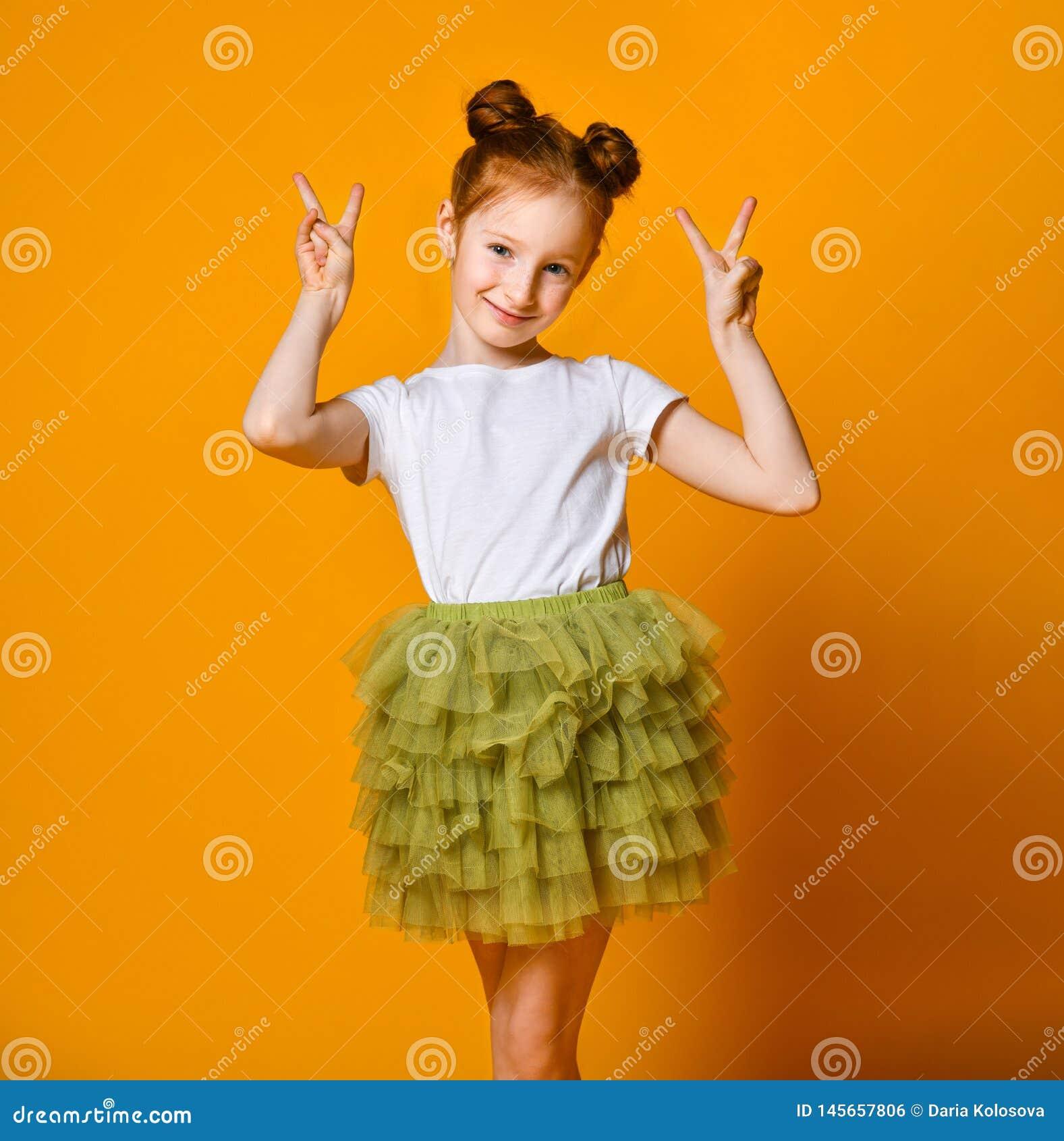 Portret van een schitterend roodharig meisje die camera met een glimlach bekijken en vredesteken met vingers tonen