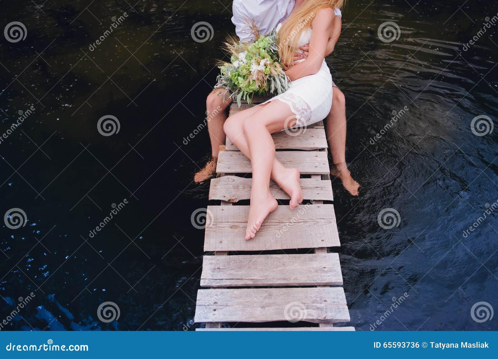 Portret van een sensueel jong paar die op een houten brug koesteren