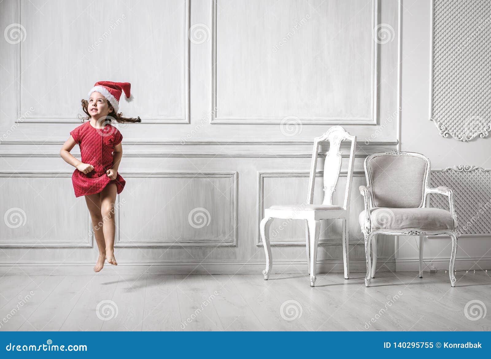 Portret van een springend meisje die een santahoed dragen