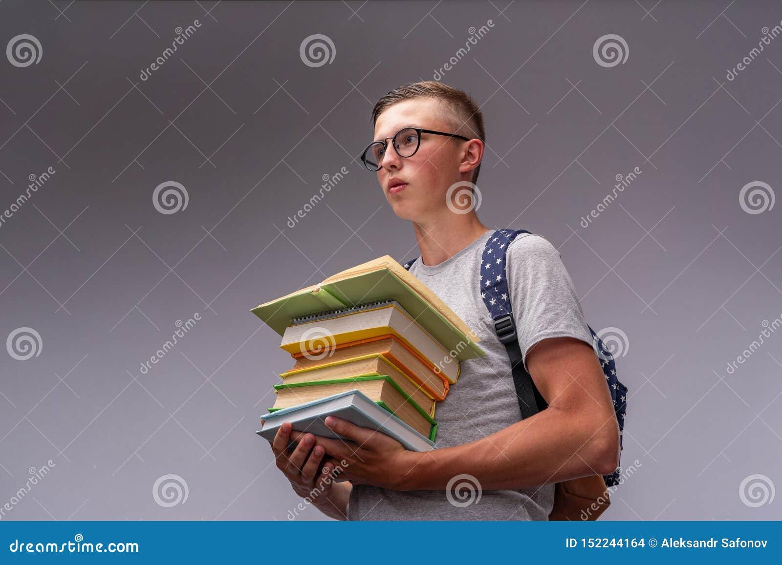 Portret van een verwarde jongensstudent met een rugzak en een stapel boeken in zijn handen, grappige positieve middelbare schoolt