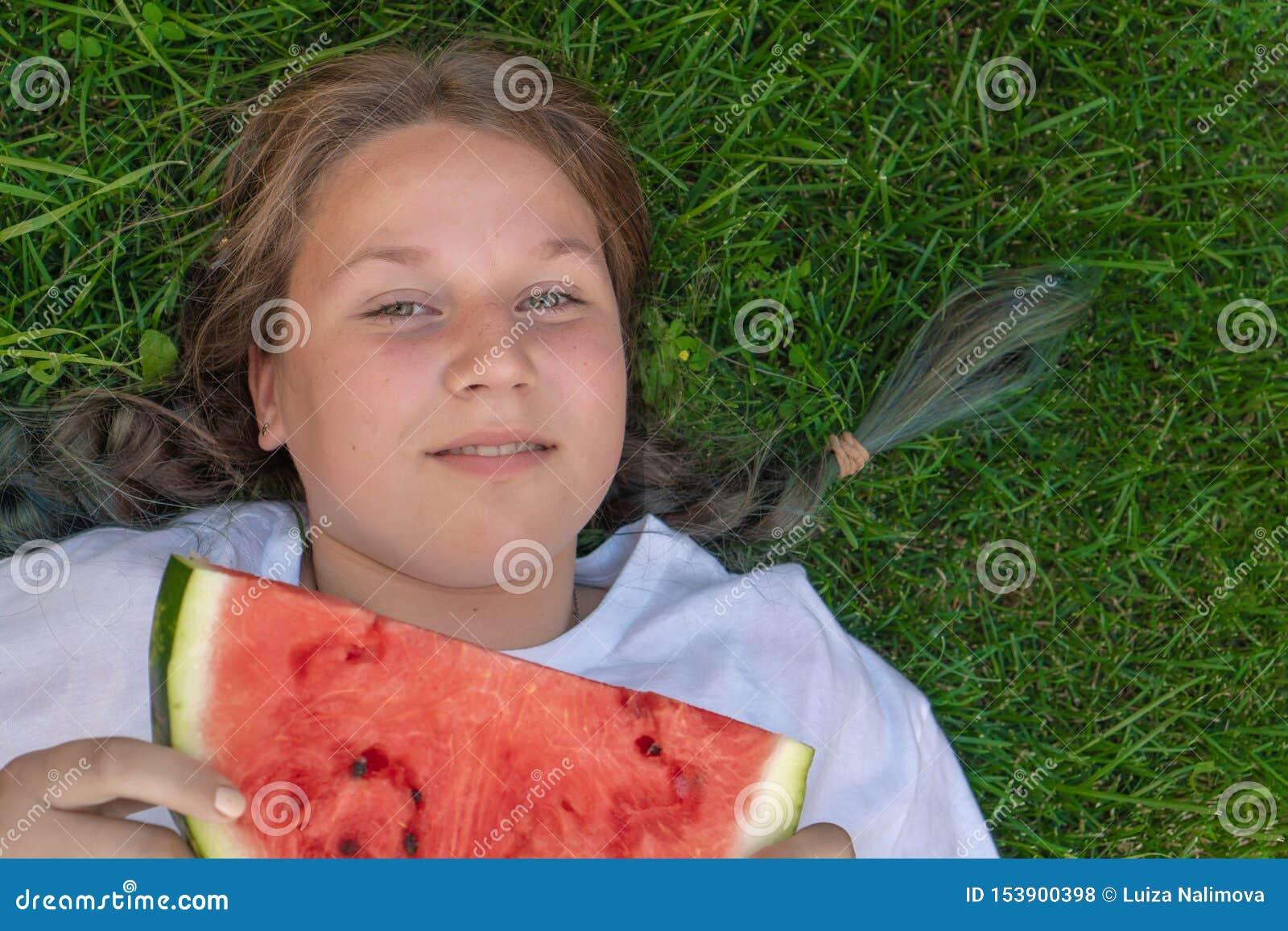 Portret van een vet meisje van 13 jaar oud wie op het gras met een watermeloen in haar handen ligt