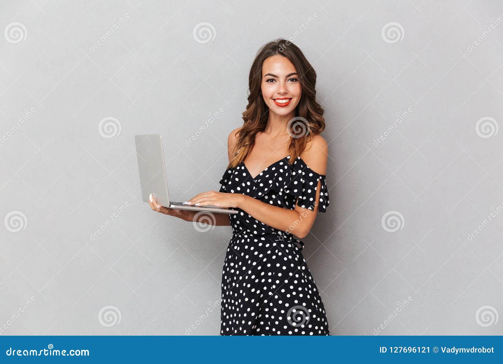 Portret van een vrolijk jong meisje in kleding over grijs