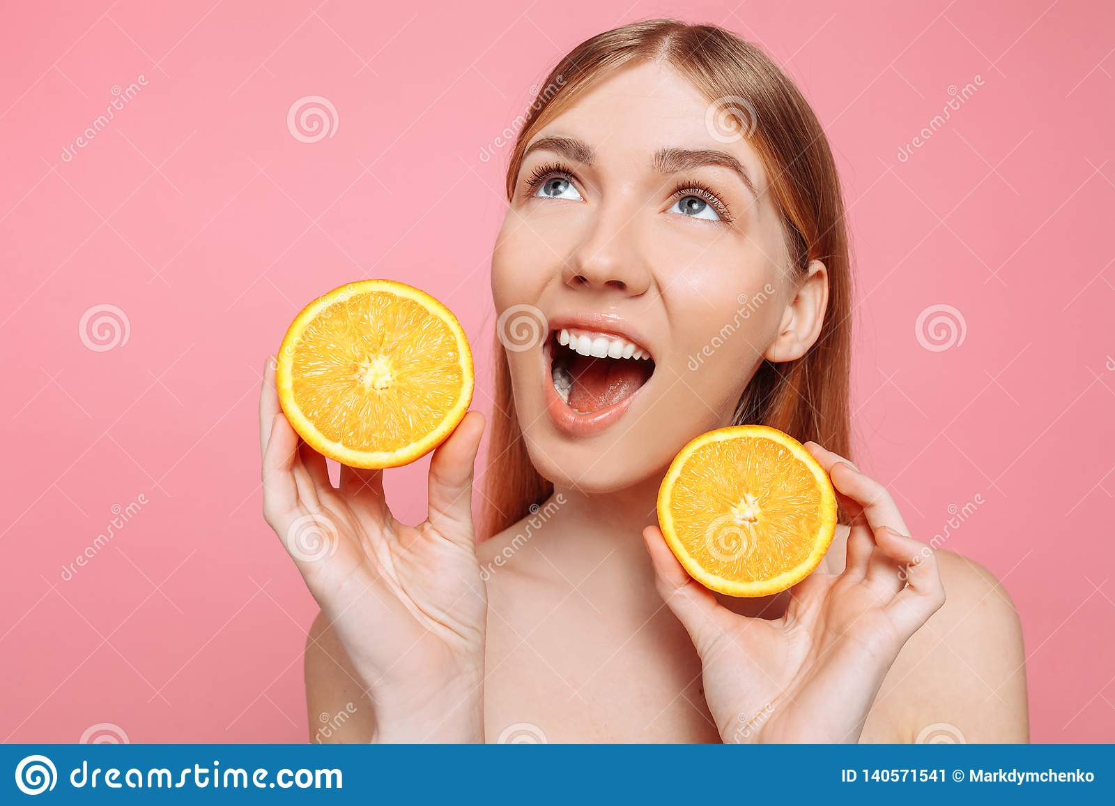 Portret van een vrolijk vrouwelijk meisje, natuurlijke duidelijke huid, meisje met twee oranje die plakken, op een roze achtergro