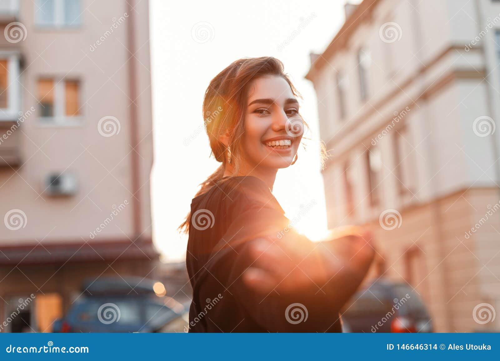 Portret van een vrolijke blije mooie jonge vrouw met een leuke glimlach in modieuze zwarte kleren in openlucht in de stad
