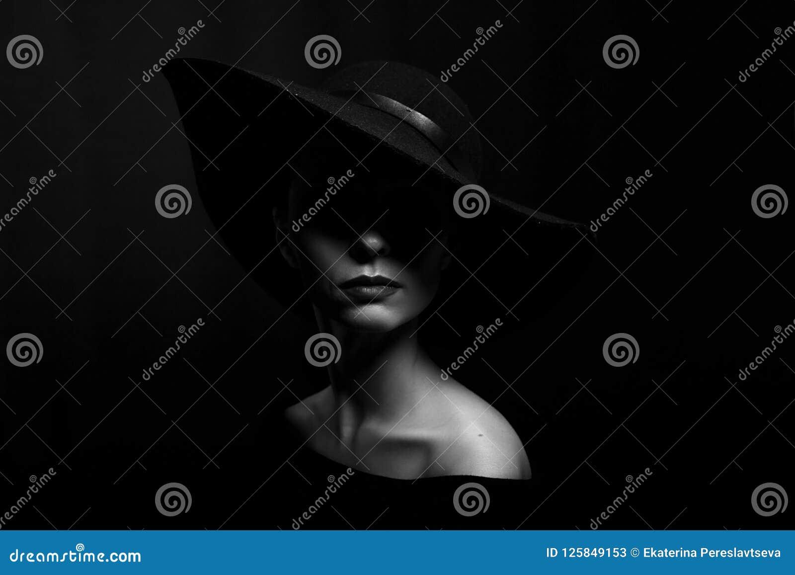Portret van een vrouw in een zwarte hoed op een zwarte zwart-witte foto als achtergrond