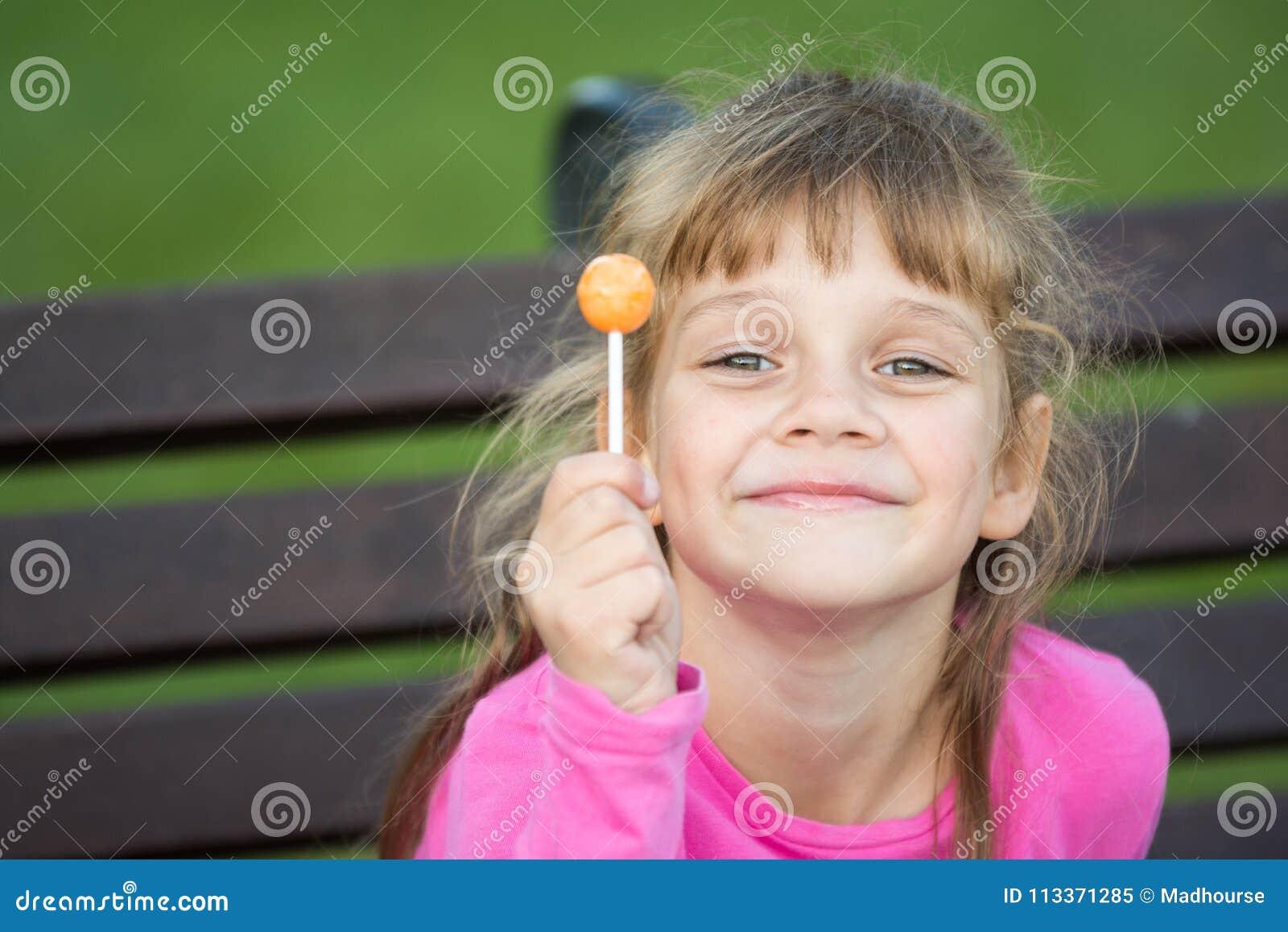 Portret van een zes-jaar-oud vrolijk meisje dat een lolly in haar hand houdt