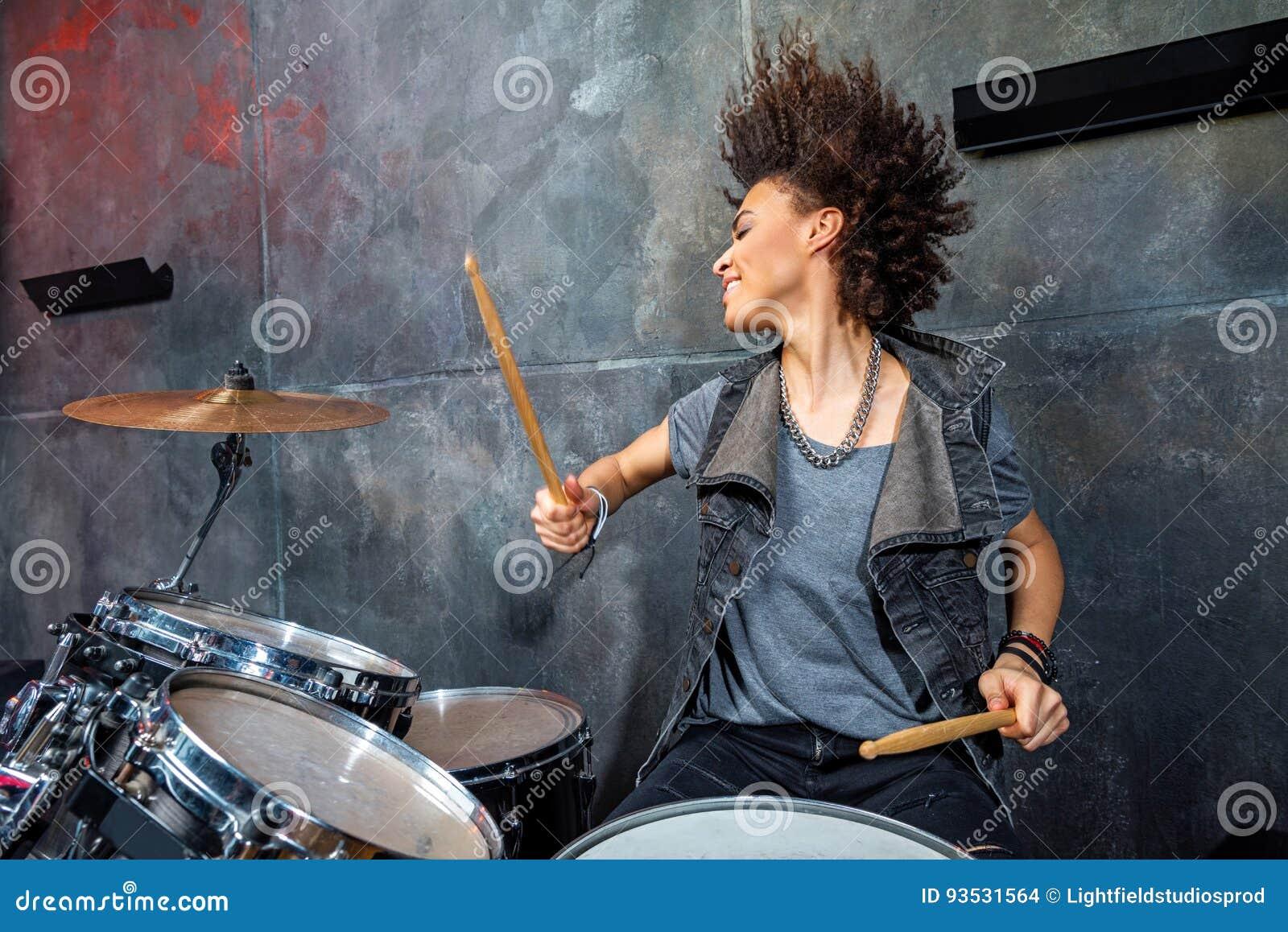 Portret van emotionele vrouw het spelen trommels in studio