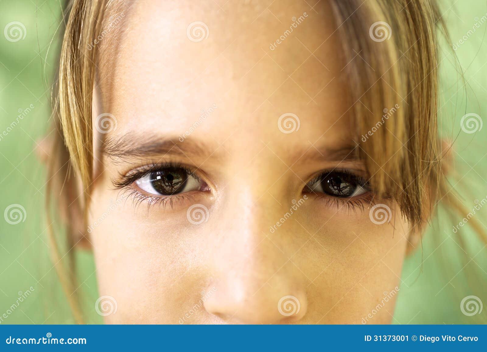 Portret van ernstig jong meisje die bij camera staren