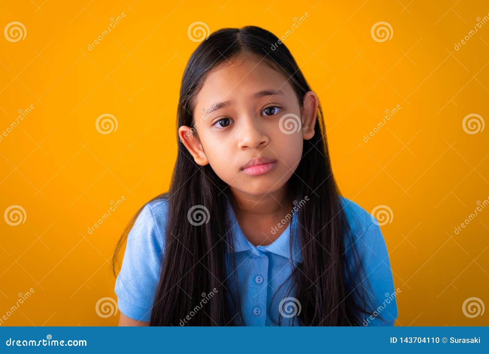 Portret van ernstige Aziatische leuke meisjes oranje achtergrond