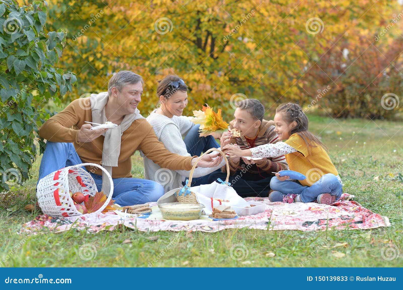 Portret van familie die een picknick in het park in de herfst hebben