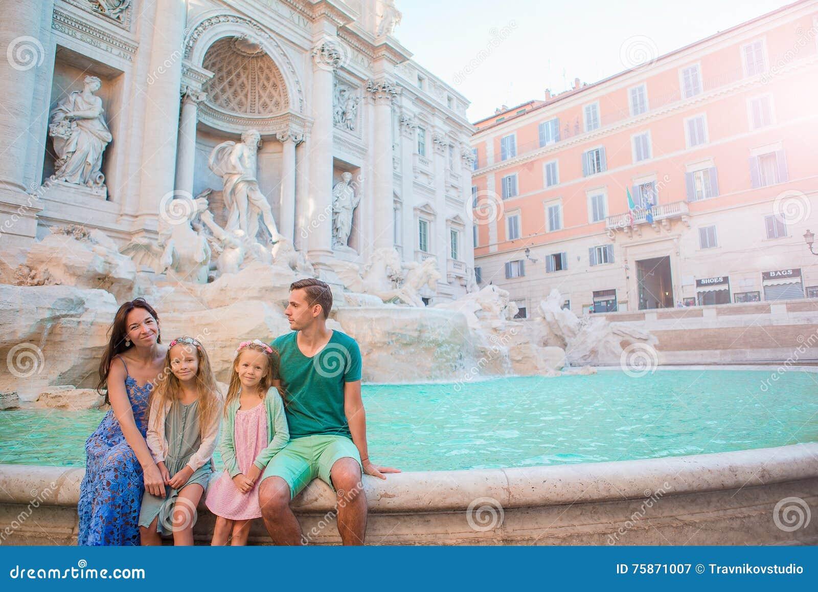 Portret van familie in Fontana Di Trevi, Rome, Italië De gelukkige ouders en de jonge geitjes genieten van Italiaanse vakantievak