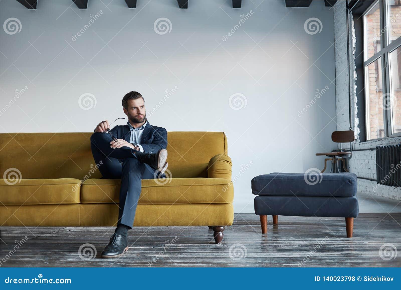 Portret van gebaarde en knappe zakenman in manierkostuum dat op bank in een modern bureau rust en binnen eruit ziet