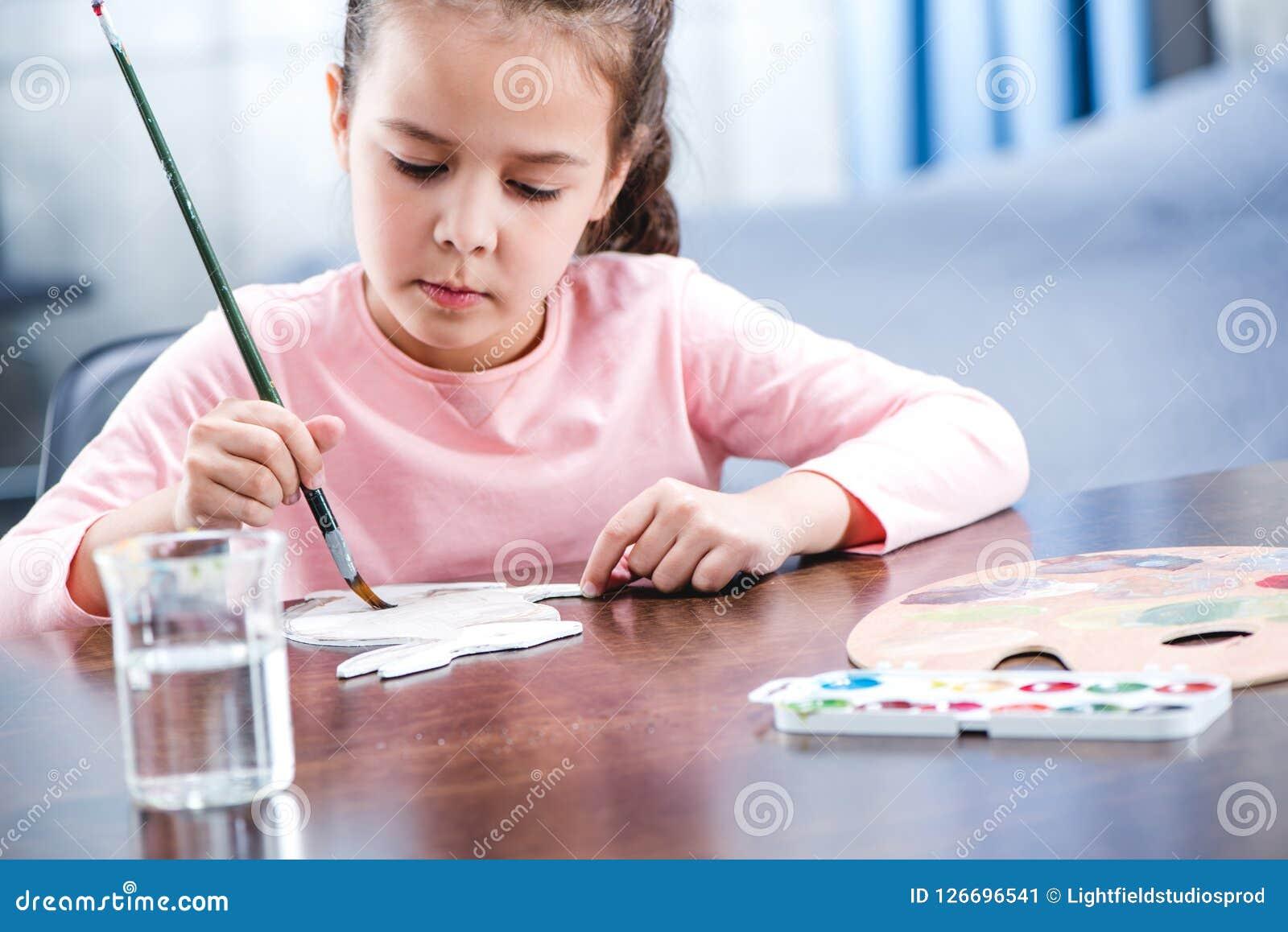 Portret van geconcentreerd kind het schilderen dier op papier