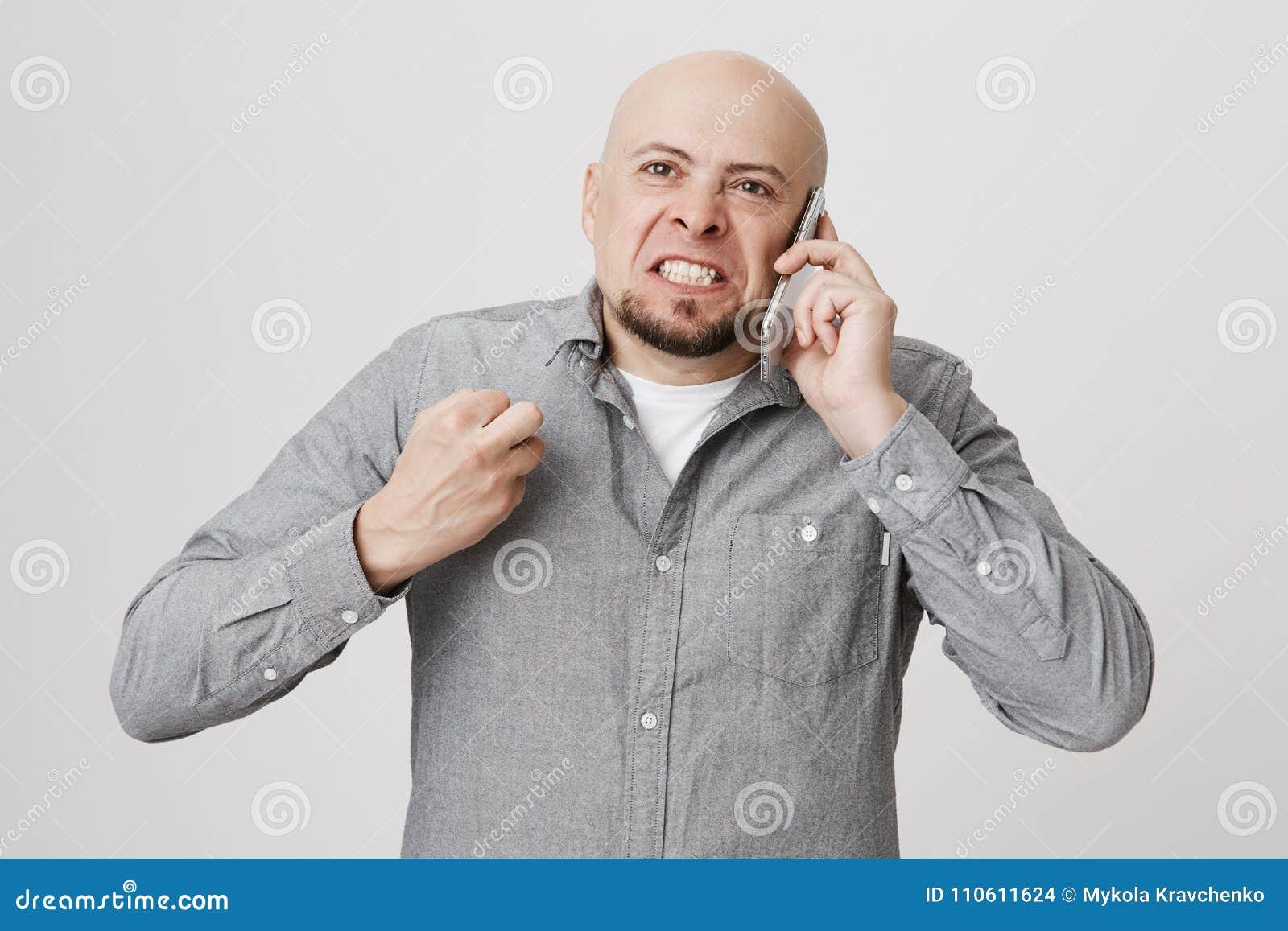 Portret van gekke kale gebaarde Kaukasische kerel die terwijl het spreken bij smartphone, het drukken van vuist van woede en het