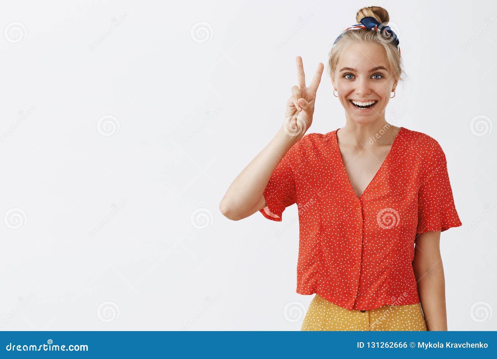 Portret van gelukkig gevoels modieus meisje met eerlijk haar in hoofdband en wijnoogst gestippelde uitrusting die overwinning ton