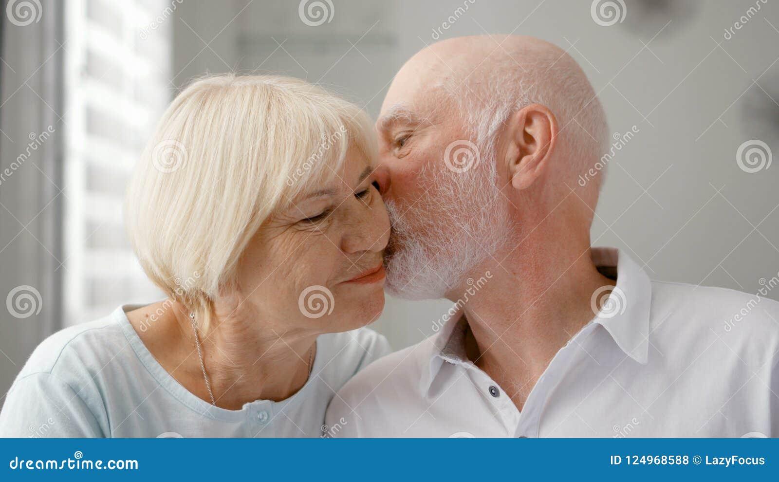 Portret van Gelukkig Hoger Paar thuis De hogere mens drukt zijn emoties uit en kust zijn vrouw