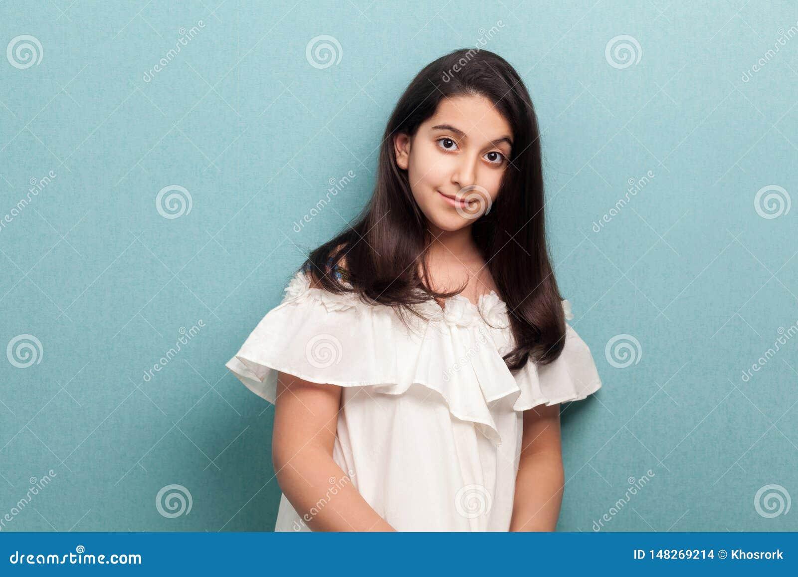 Portret van gelukkig kalm mooi donkerbruin jong meisje met zwart lang recht haar in witte kleding die en zich camera bevinden bek
