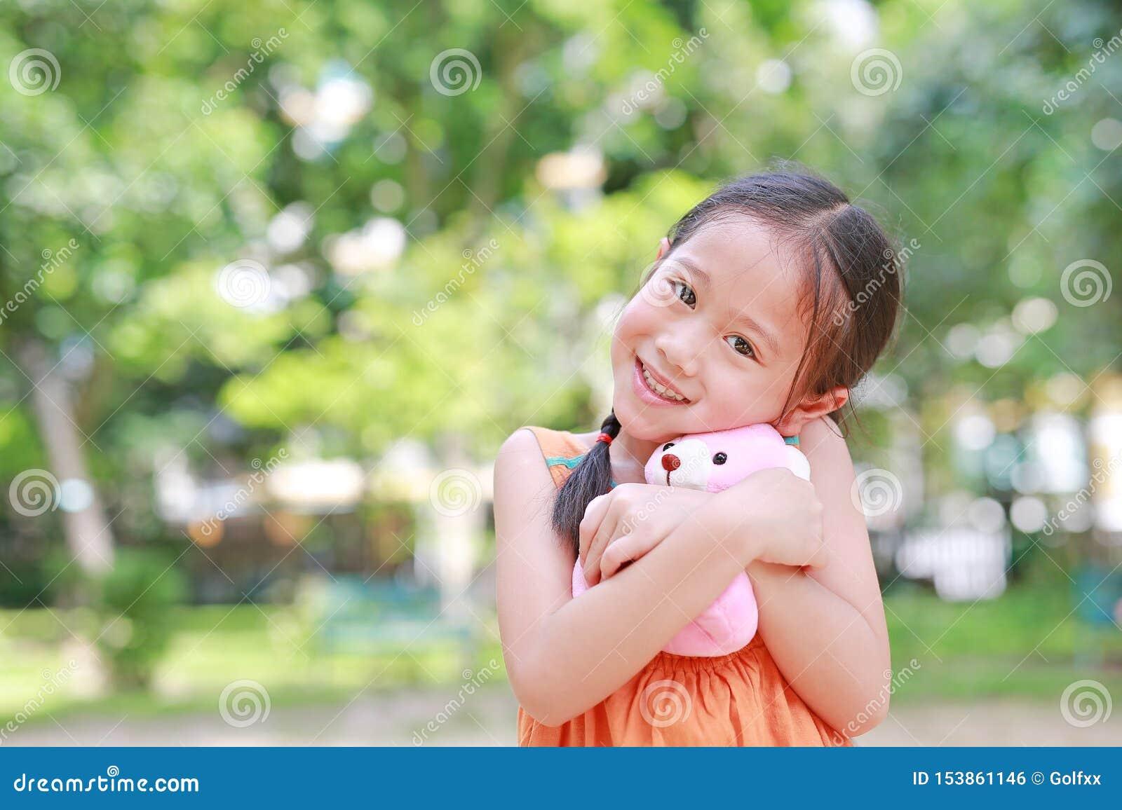 Portret van gelukkig weinig Aziatisch kind in groene tuin met het koesteren van teddybeer en het bekijken camera Kom omhoog gliml