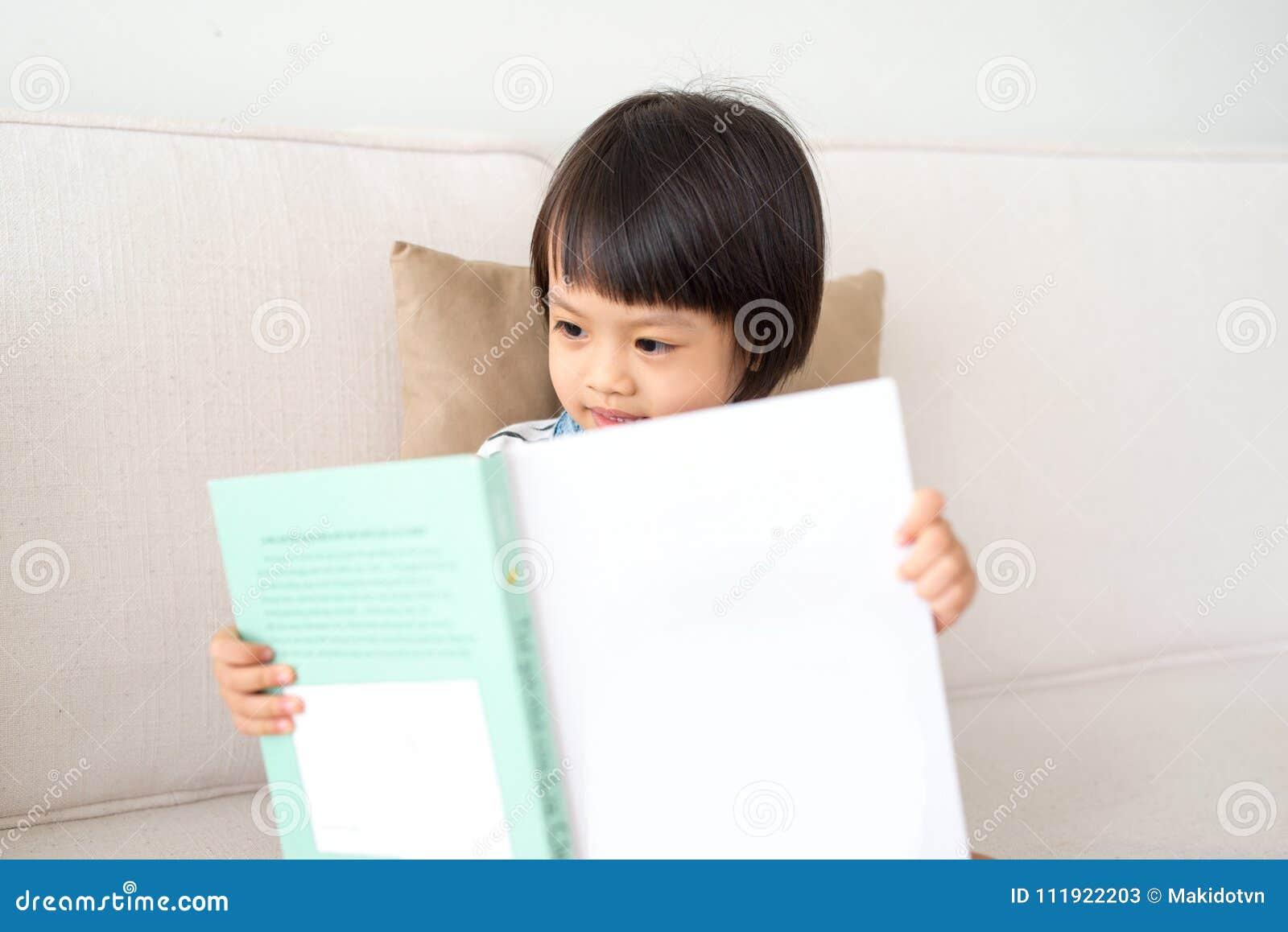 Portret van gelukkige Aziaat weinig de lezingsboek van het kindmeisje