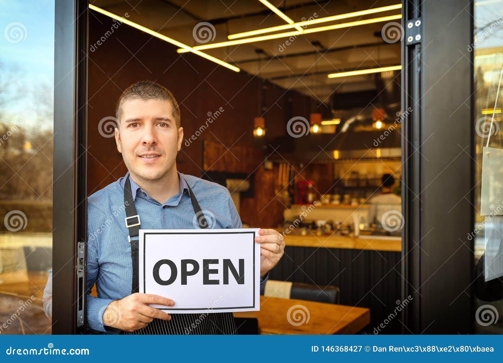 Portret van gelukkige bedrijfseigenaar die open teken houden - Jonge mensenondernemer bij ingang van nieuwe kleine familierestaur