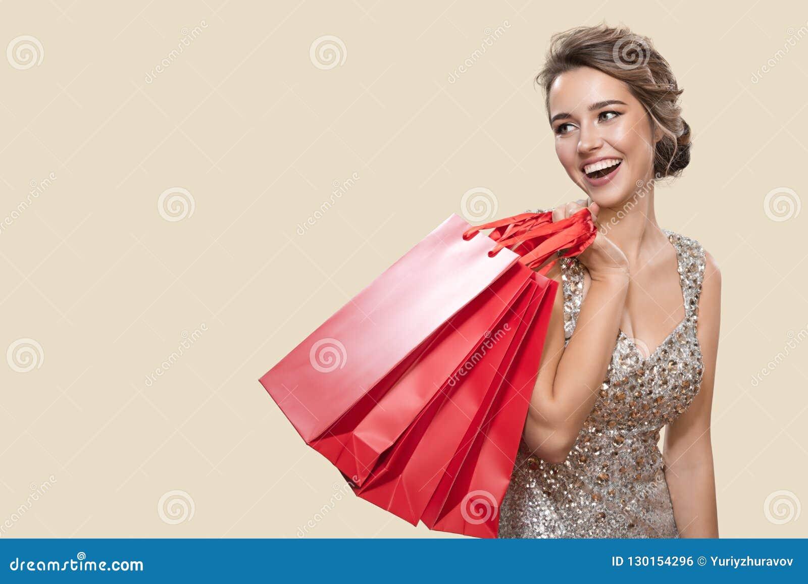 Portret van gelukkige charmante vrouw die rode het winkelen zakken houden