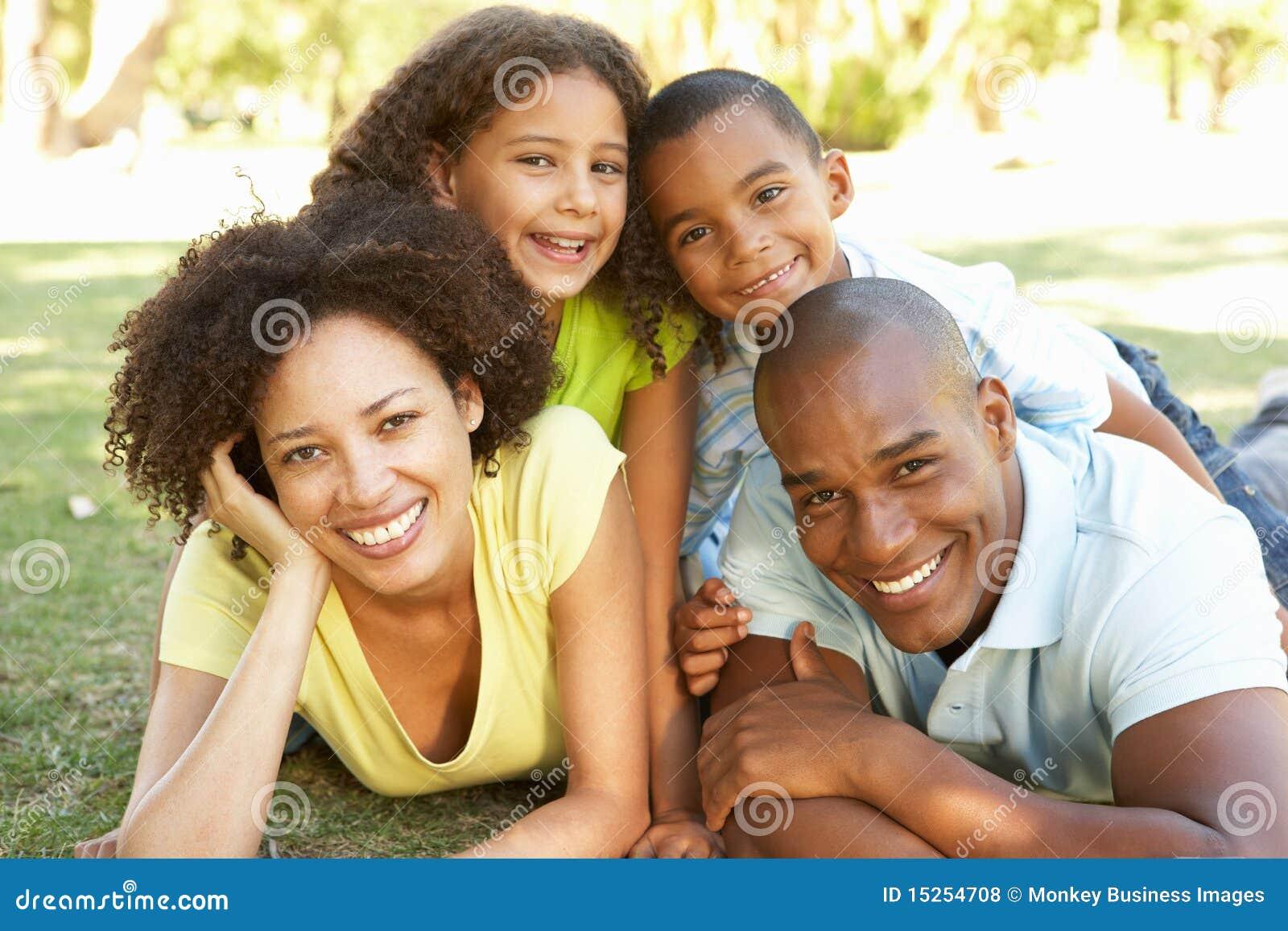 Portret van Gelukkige Familie dat omhoog in Park wordt opgestapeld