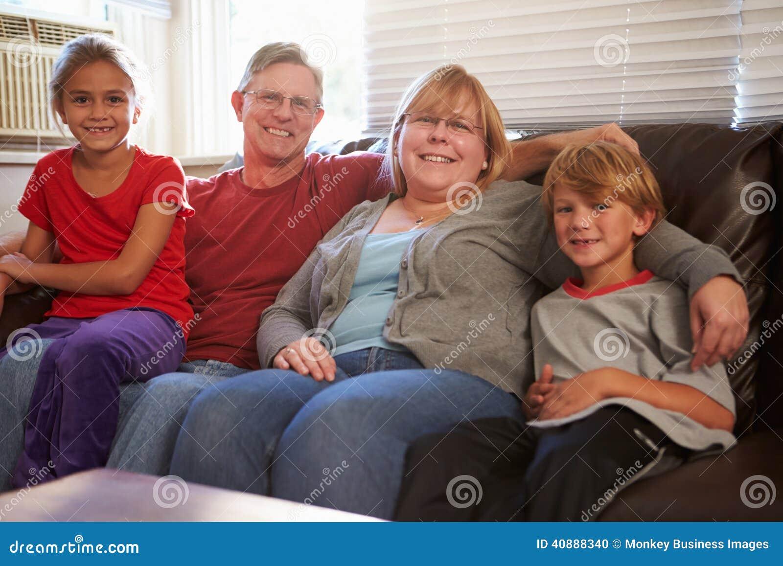 Portret van gelukkige familiezitting op bank samen