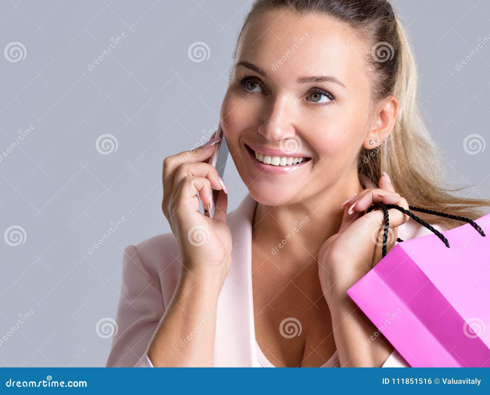 Portret van gelukkige glimlachende vrouw met roze zak die op A.M. spreekt