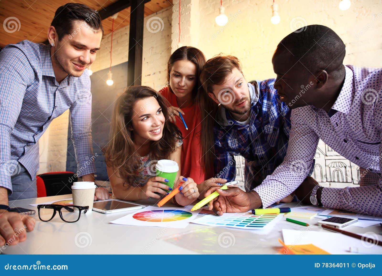 Portret van gelukkige jongeren in een vergadering die camera en het glimlachen bekijken Jonge ontwerpers die aan a samenwerken