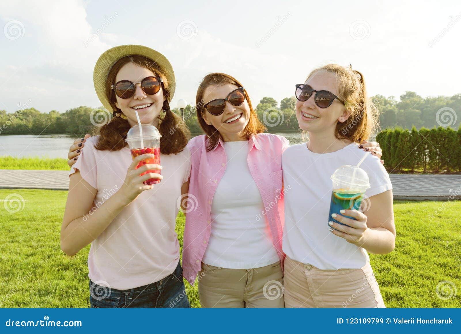Portret van gelukkige moeder en dochterstieners 14 en 16 jaar oud, meisjes met de zomerdranken Achtergrondaard, recreatiegebied