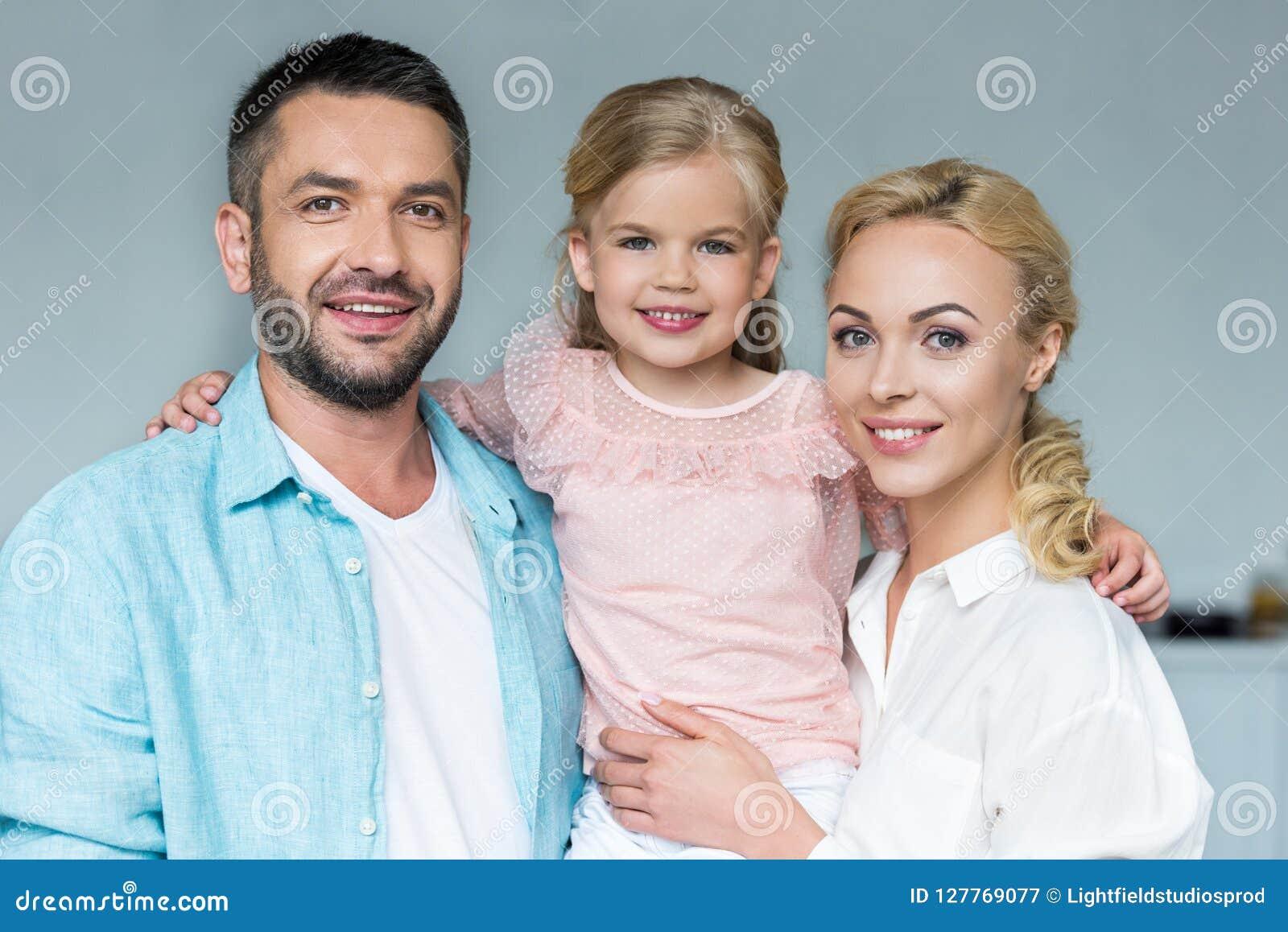 Portret van gelukkige ouders met aanbiddelijk weinig dochter het glimlachen