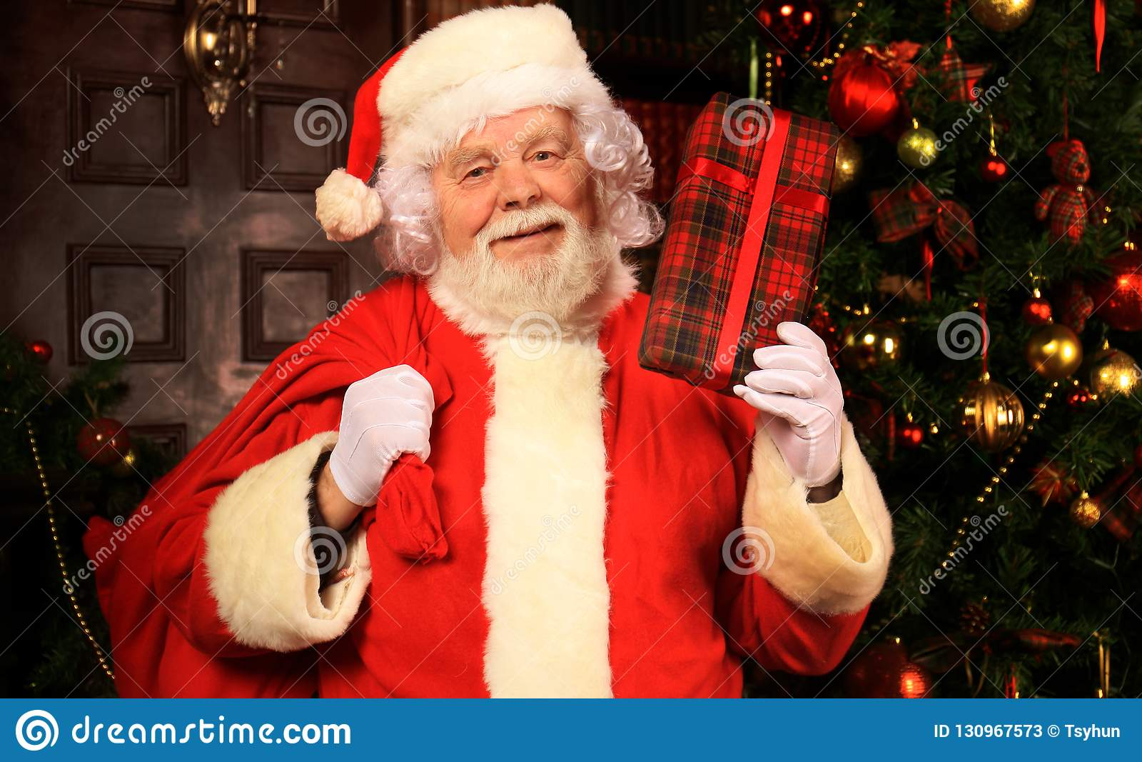 Portret van gelukkige Santa Claus bij zijn ruimte thuis dichtbij Kerstboom met giftdoos