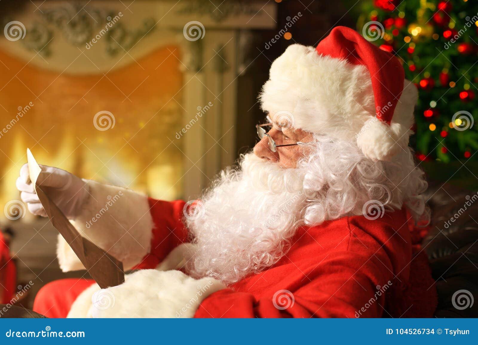 Portret van gelukkige Santa Claus-zitting bij zijn ruimte thuis dichtbij Kerstboom en de brief van lezingskerstmis of wenslijst